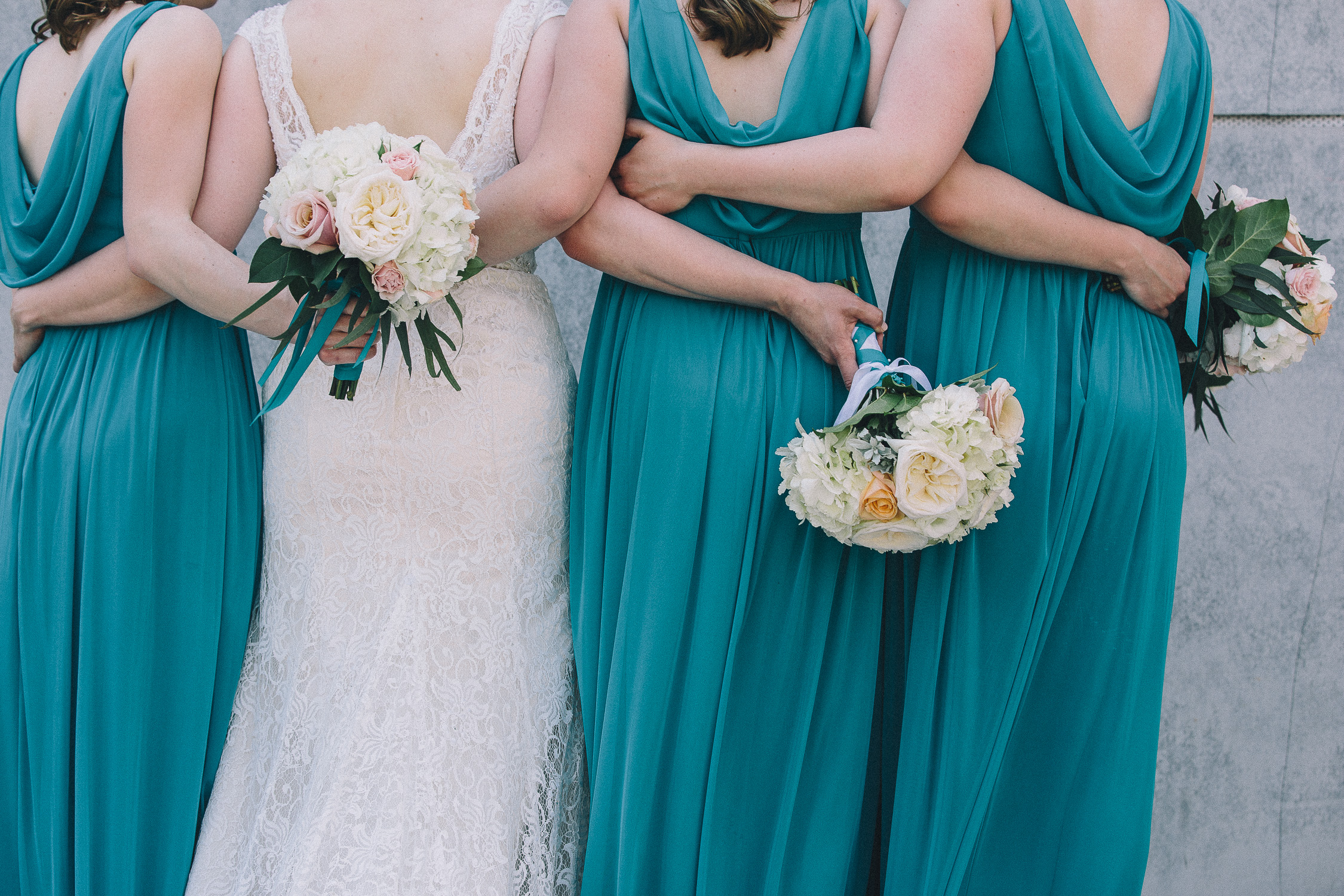 Bride wearing a low-back lace wedding gown links arms around the waists of her bridesmaids wearing teal dresses