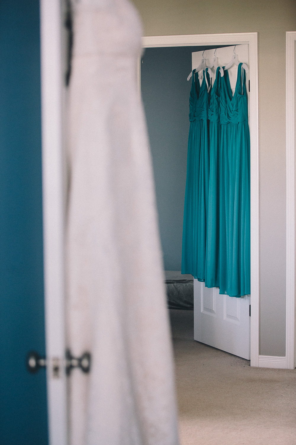 Teal bridesmaid dresses hanging on door with wedding dress in the foreground.