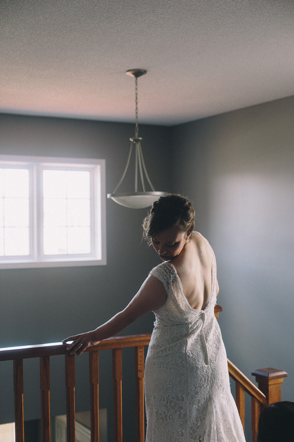 Bride with short hair stands against stair railing to show her low back lace wedding gown
