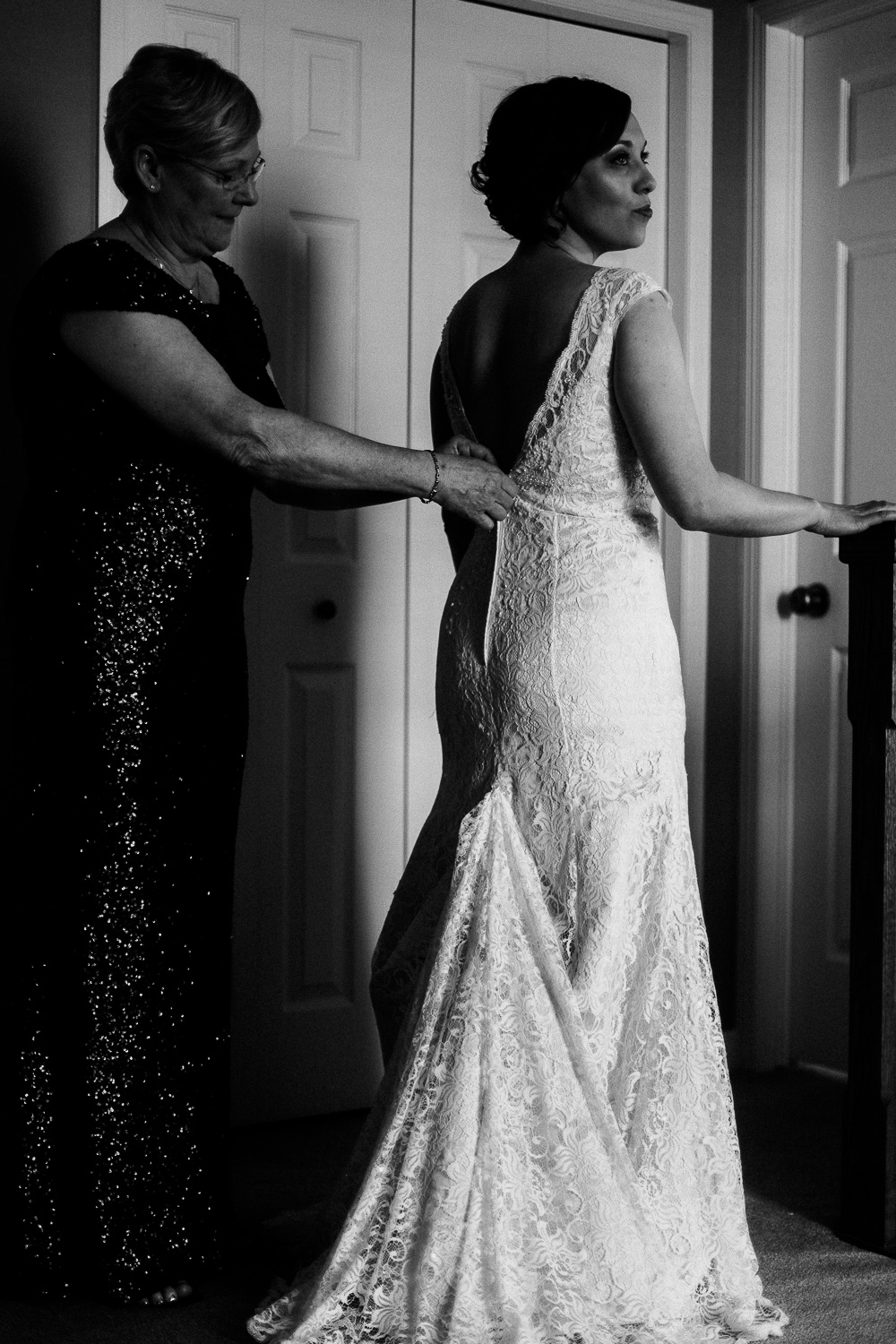 Mother of the bride zipping up the back of bride's low-back lace dress