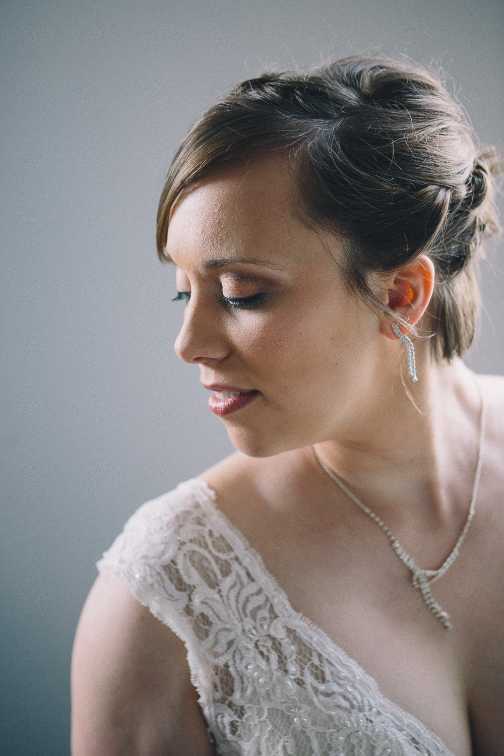 Bride with short hair looks over her shoulder to show the lace detail of her wedding gown and natural makeup