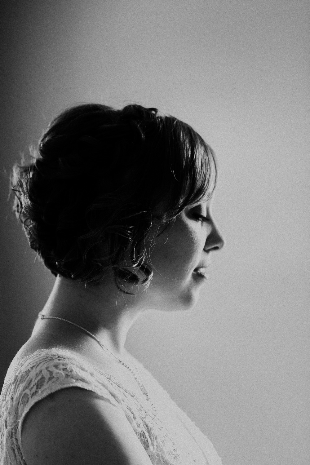 Bride with short hair stands profile to show her natural hairstyle and lace detail of her wedding gown