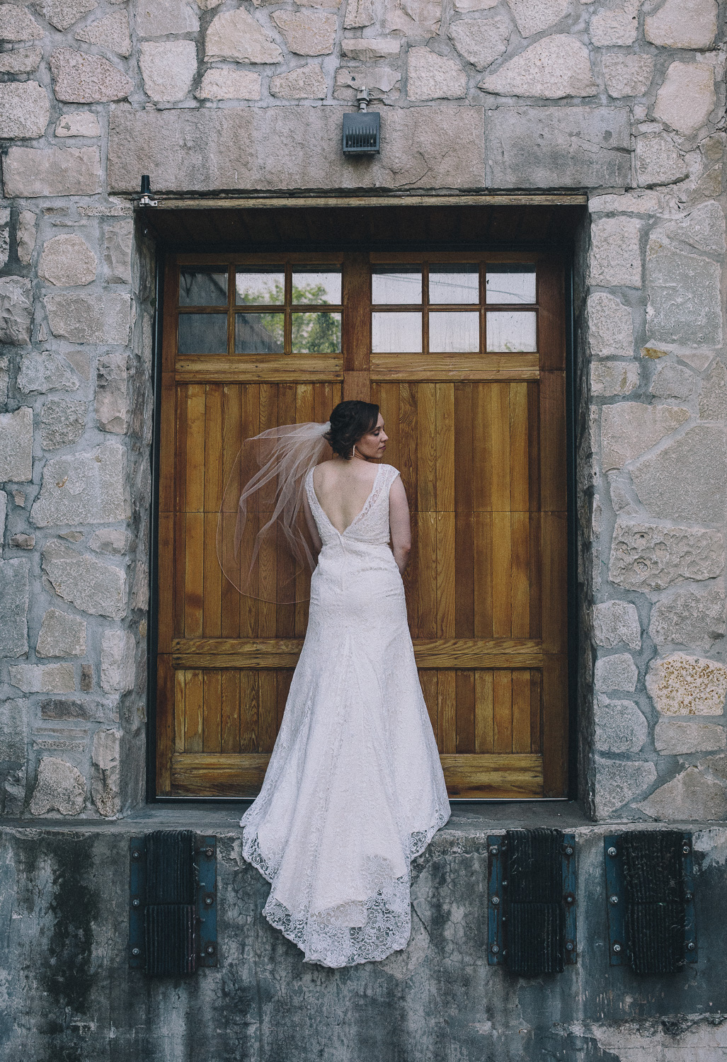 Bride with short hair stands to show her low back lace wedding gown and low-set veil against the shipping door at the Cambridge Mill