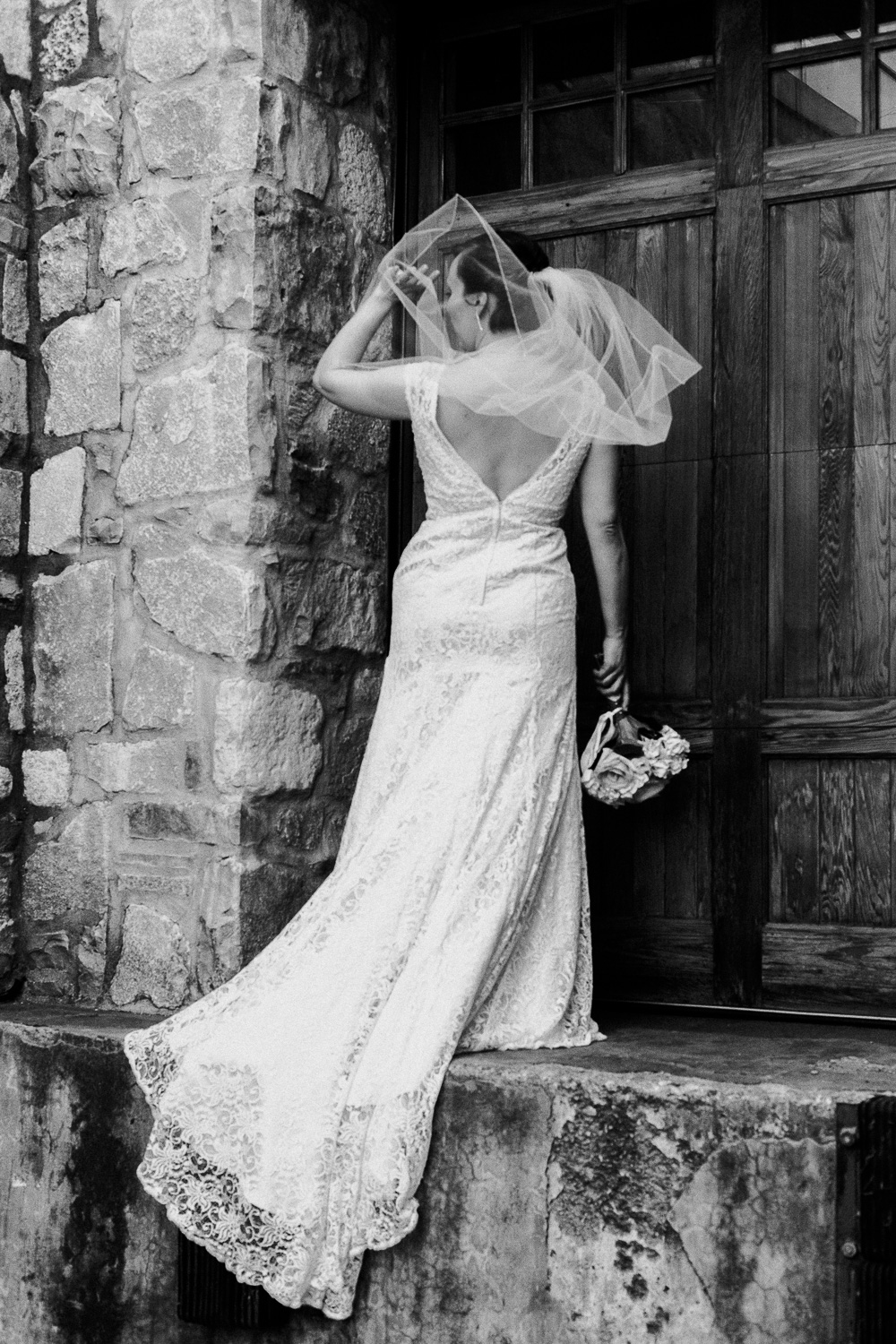 Bride with short hair stands to show her low back lace wedding gown and low-set veil at the Cambridge Mill