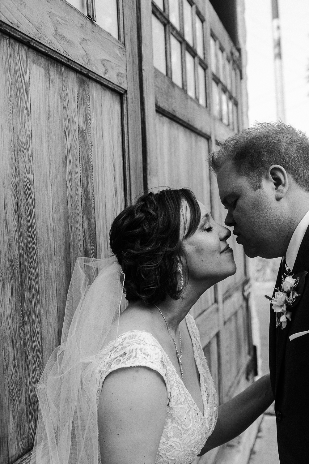 Bride with short hair and low-set veil leans in to kiss her groom at the Cambridge Mill during their summer wedding