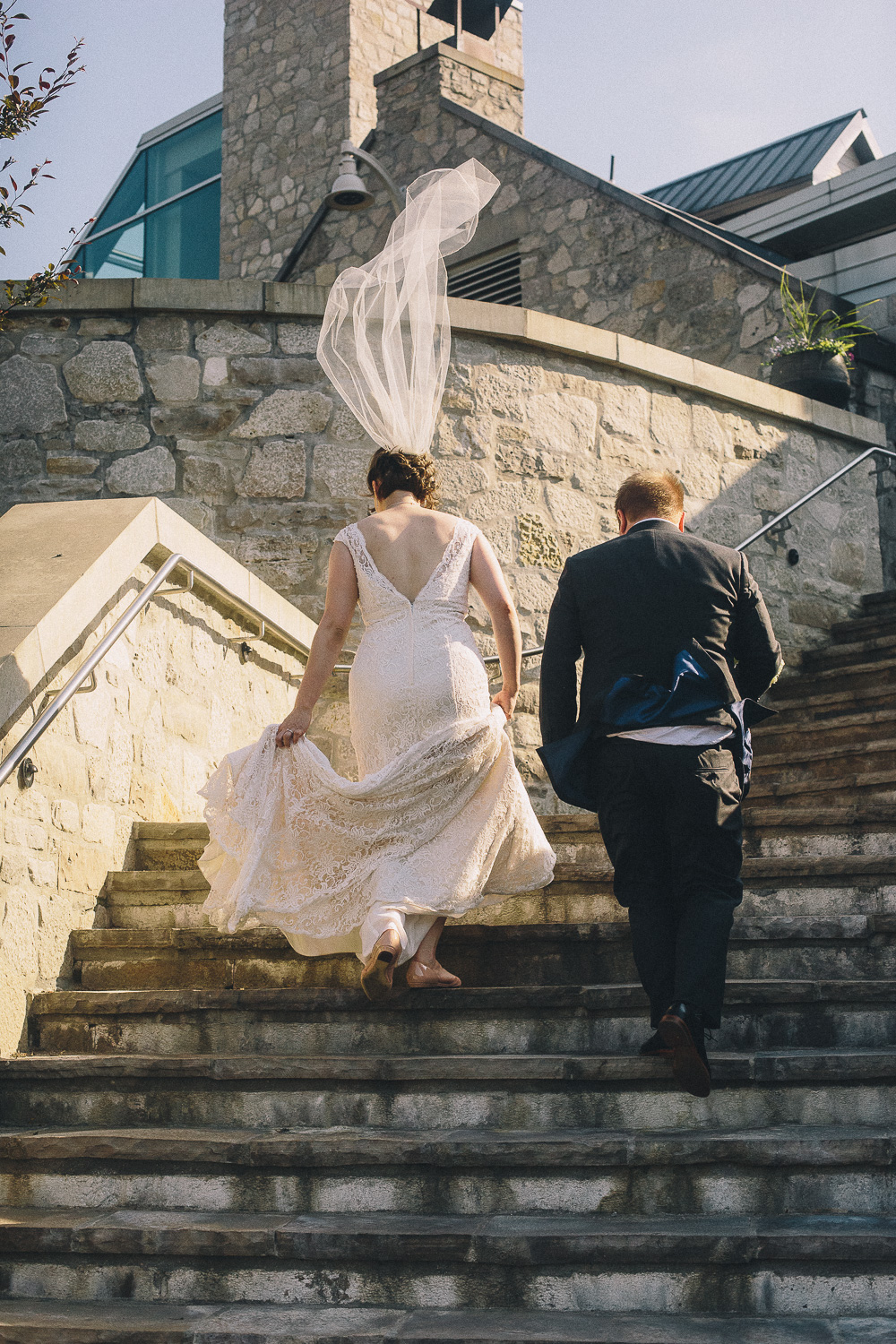 Bride with short hair stands to show her low back lace wedding gown and low-set veil walks up the steps at the Cambridge Mill with her groom during their summer Christian wedding