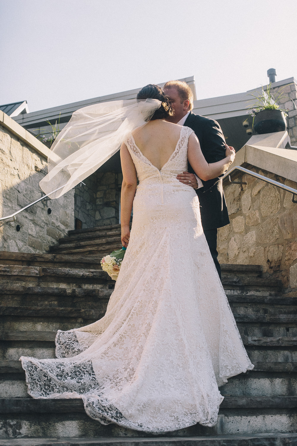 Bride with short hair stands to show her low back lace wedding gown and low-set veil while her groom holds her waist and kisses her cheek on the steps at the Cambridge Mill
