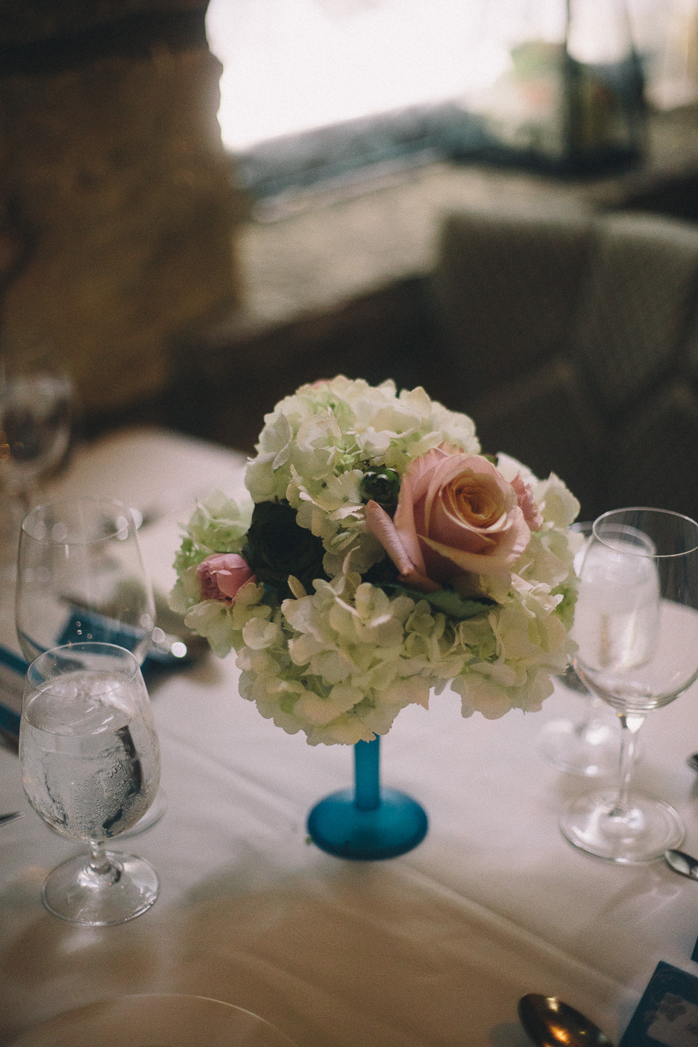 Simple floral centrepiece at summer wedding reception at Cambridge Mill
