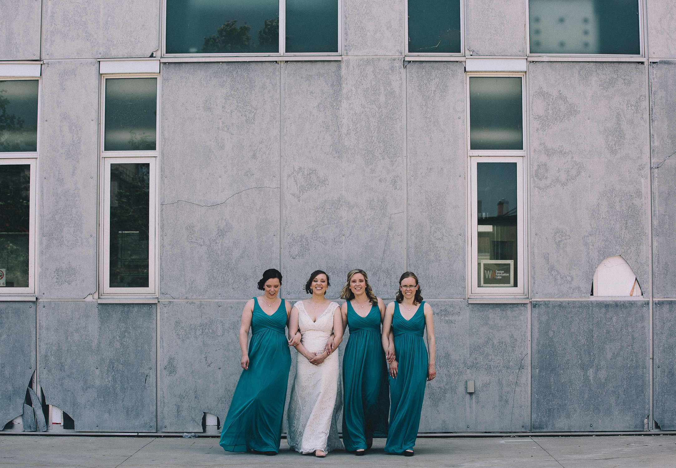 Bride in lace wedding gown and bridesmaids wearing teal dresses walking in downtown Cambridge during a summer wedding