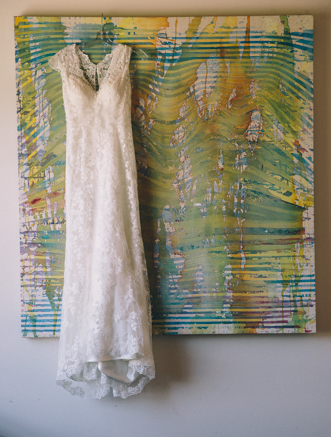 Lace wedding dress hanging on an abstract tropical painting at Hotel Ocho in Toronto