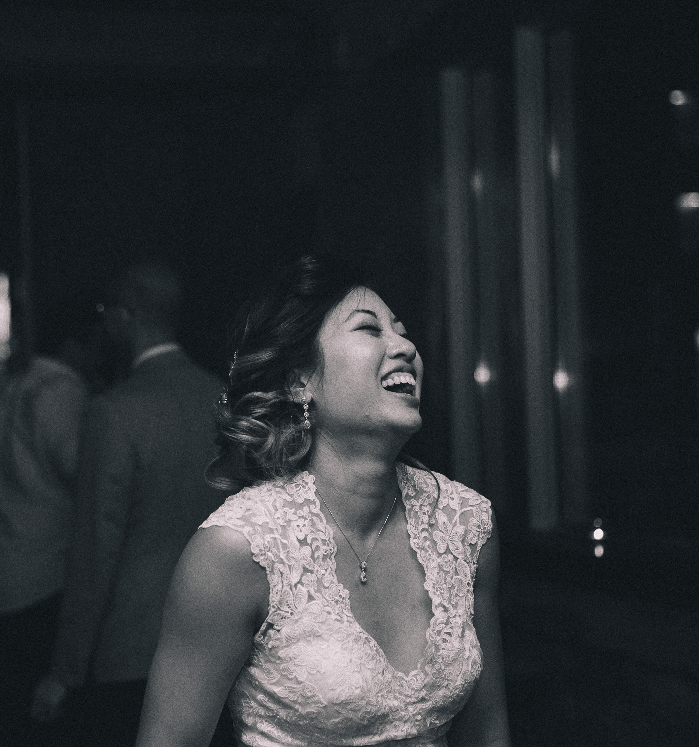 Candid image of an Asian bride wearing a lace wedding gown with loose up-do to the side laughing during the reception at Hotel Ocho