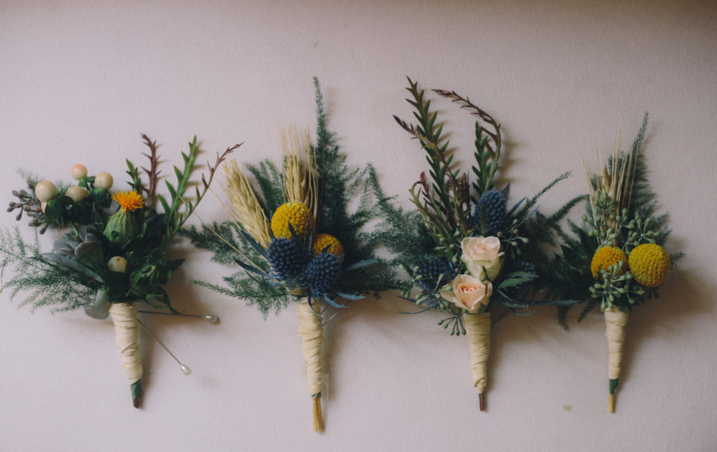 Four fresh greenery and dried blooms boutonierres tied with twine line up on a surface at Hotel Ocho