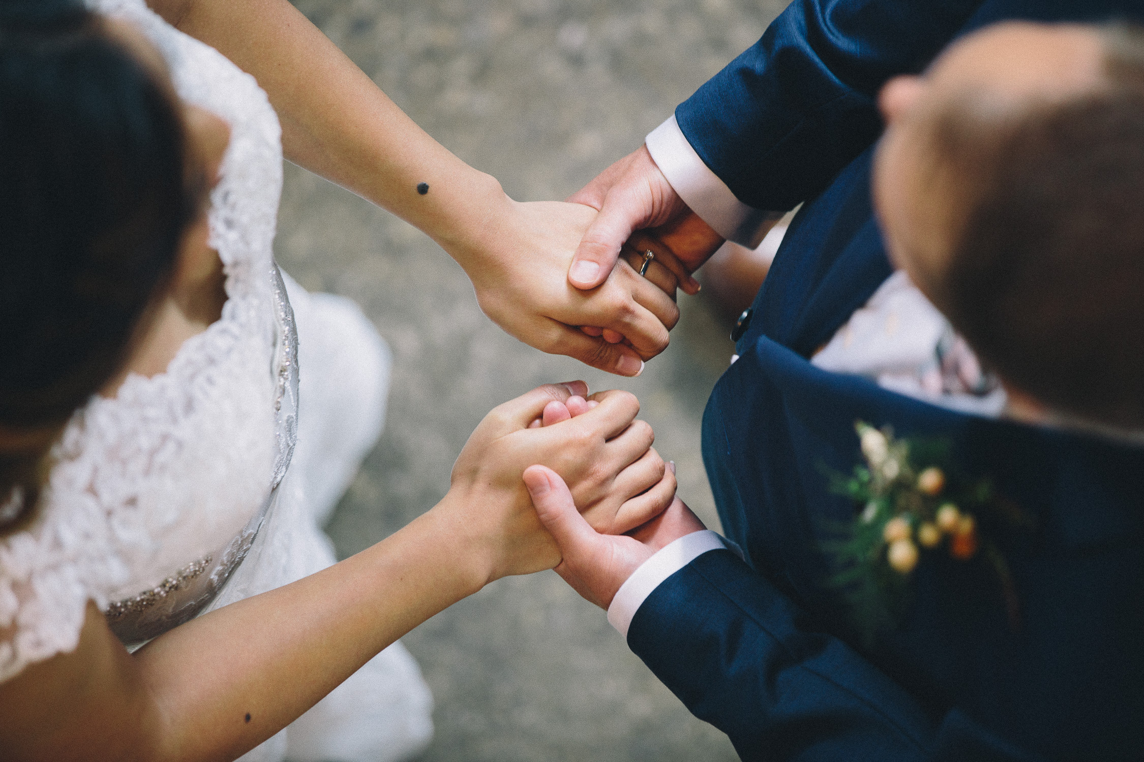 Interracial bride and groom hold hands during their non-religious wedding ceremony at Hotel Ocho