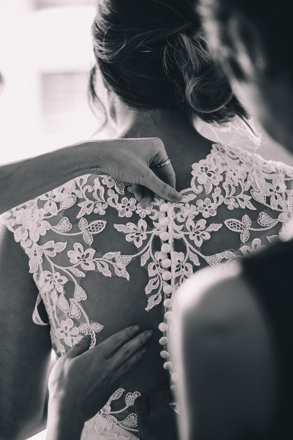 Two feminine hands of the maid of honour buttoning up the bride's lace wedding dress at Hotel Ocho