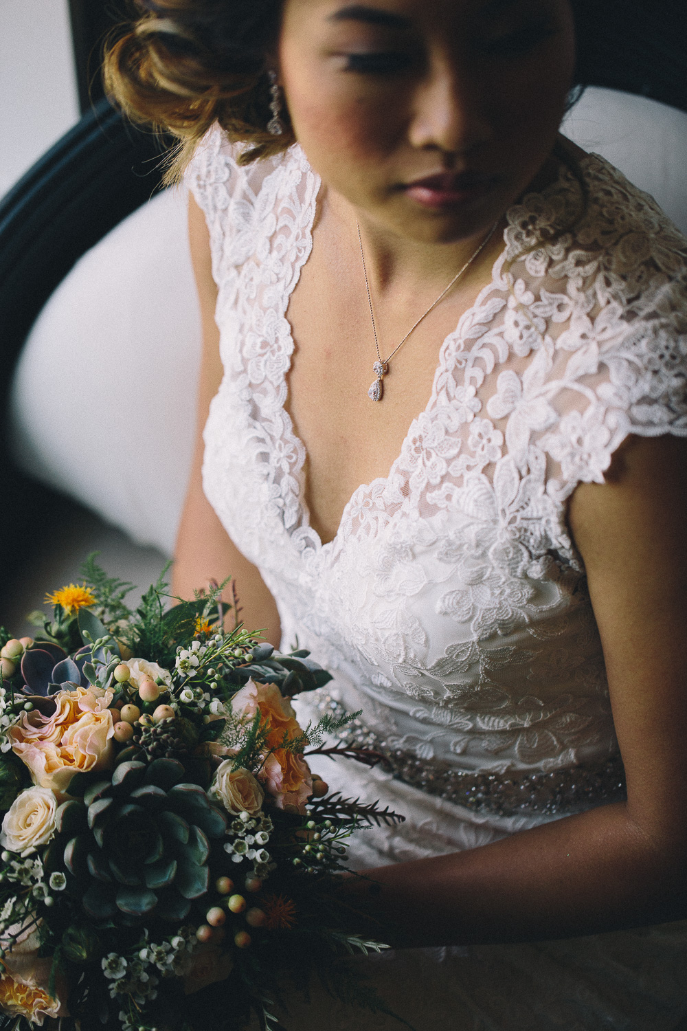Asian bride wearing v-neck lace wedding gown and tear drop diamond necklace and earrings holds her succulent bridal bouquet at Hotel Ocho after getting ready