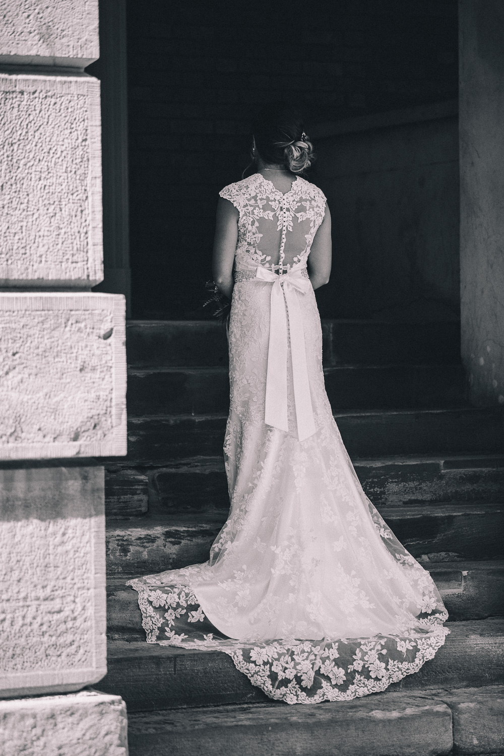 Asian bride stands to show the back of her slim fit lace wedding gown with low back small train and bow detail at Osgoode Hall