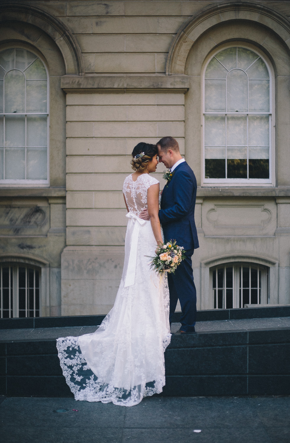Groom wearing navy wedding suit holds his Asian bride around the waist as she shows the back of her lace wedding down with low back and bow detail at Osgoode Hall
