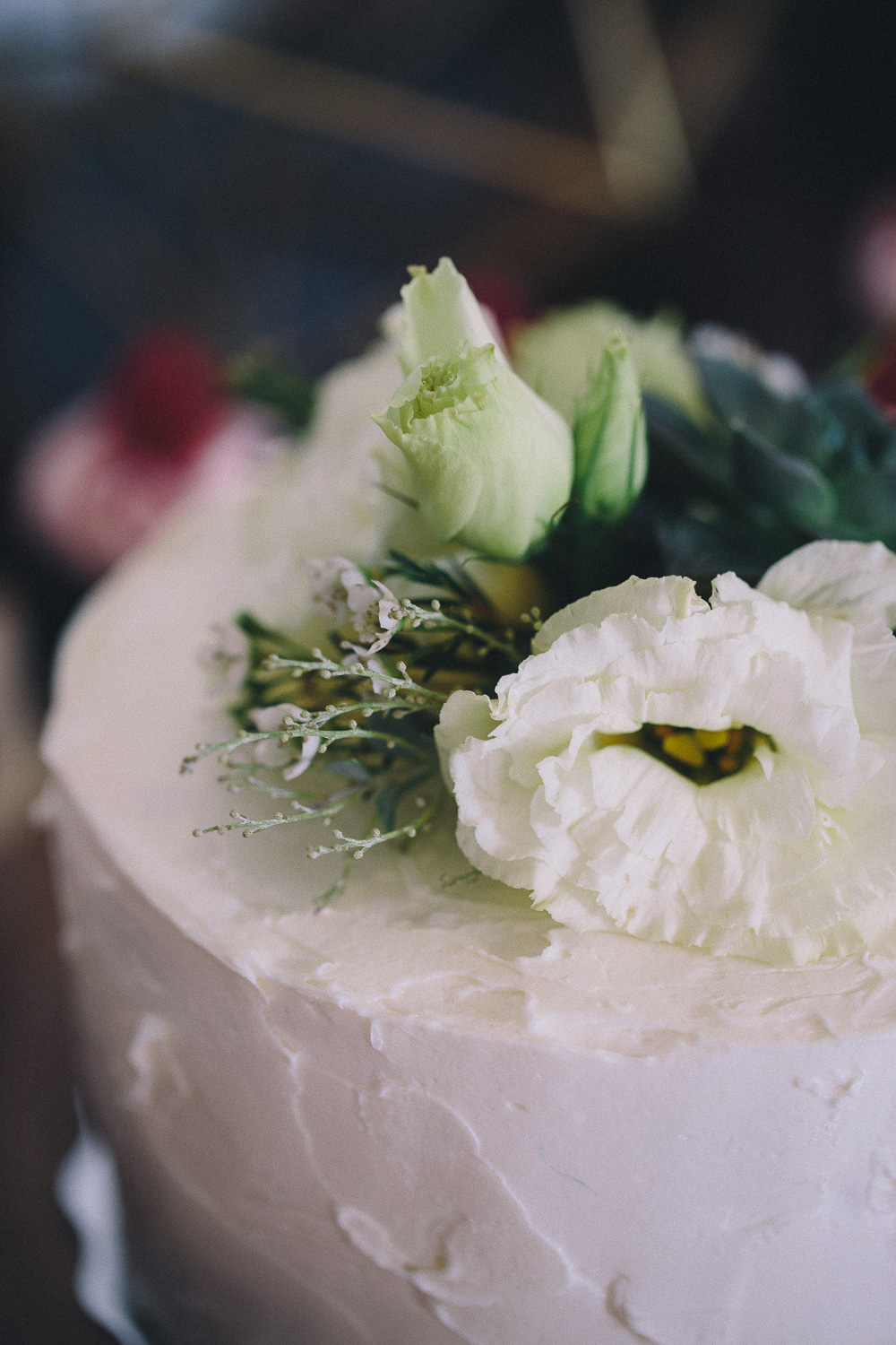 Fresh anemone sits on top of a roughly frosted wedding cake at Hotel Ocho
