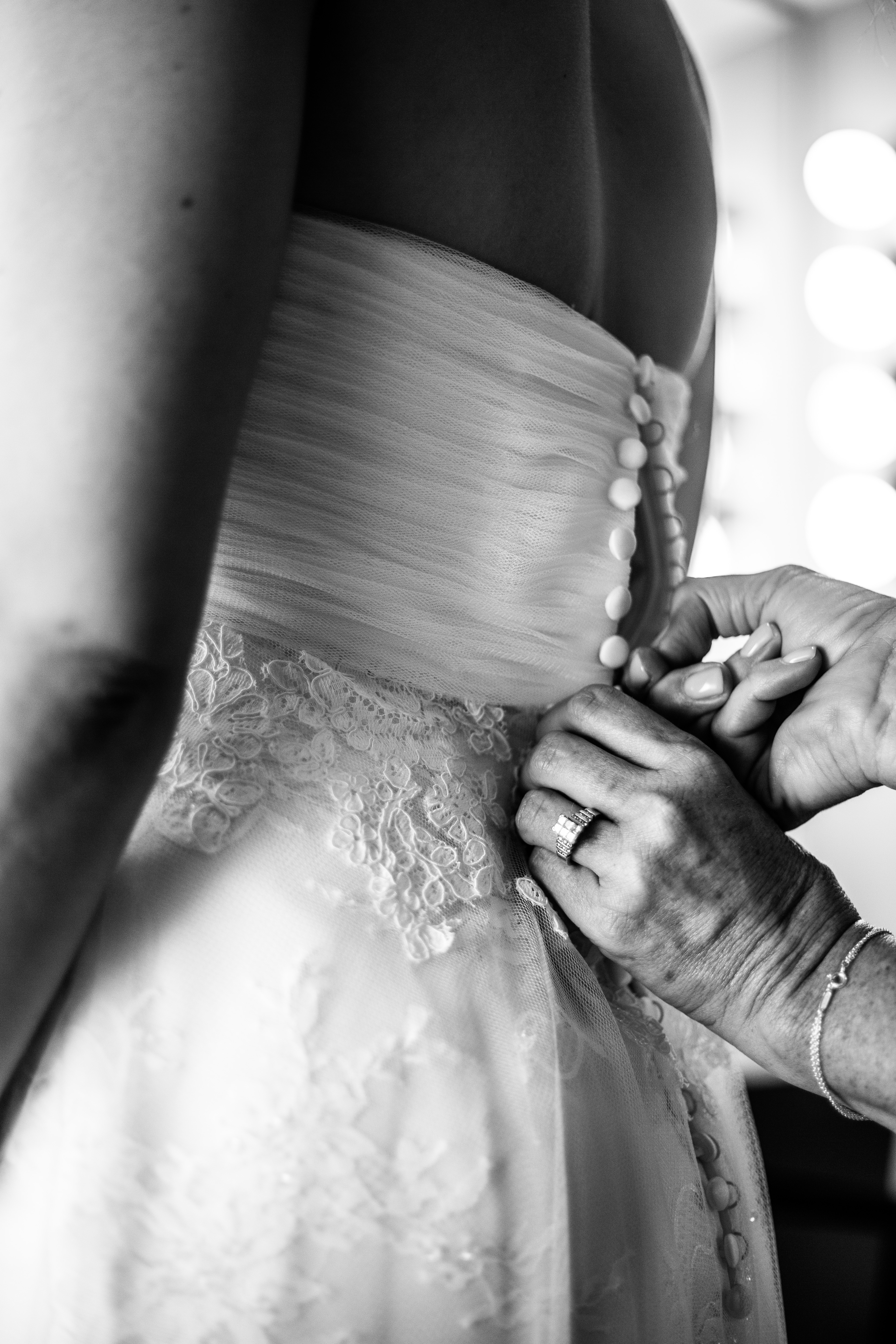 Black and white close up image of the mother of the bride's hands buttoning up the bride's sweetheart neckline wedding gown with lace detail