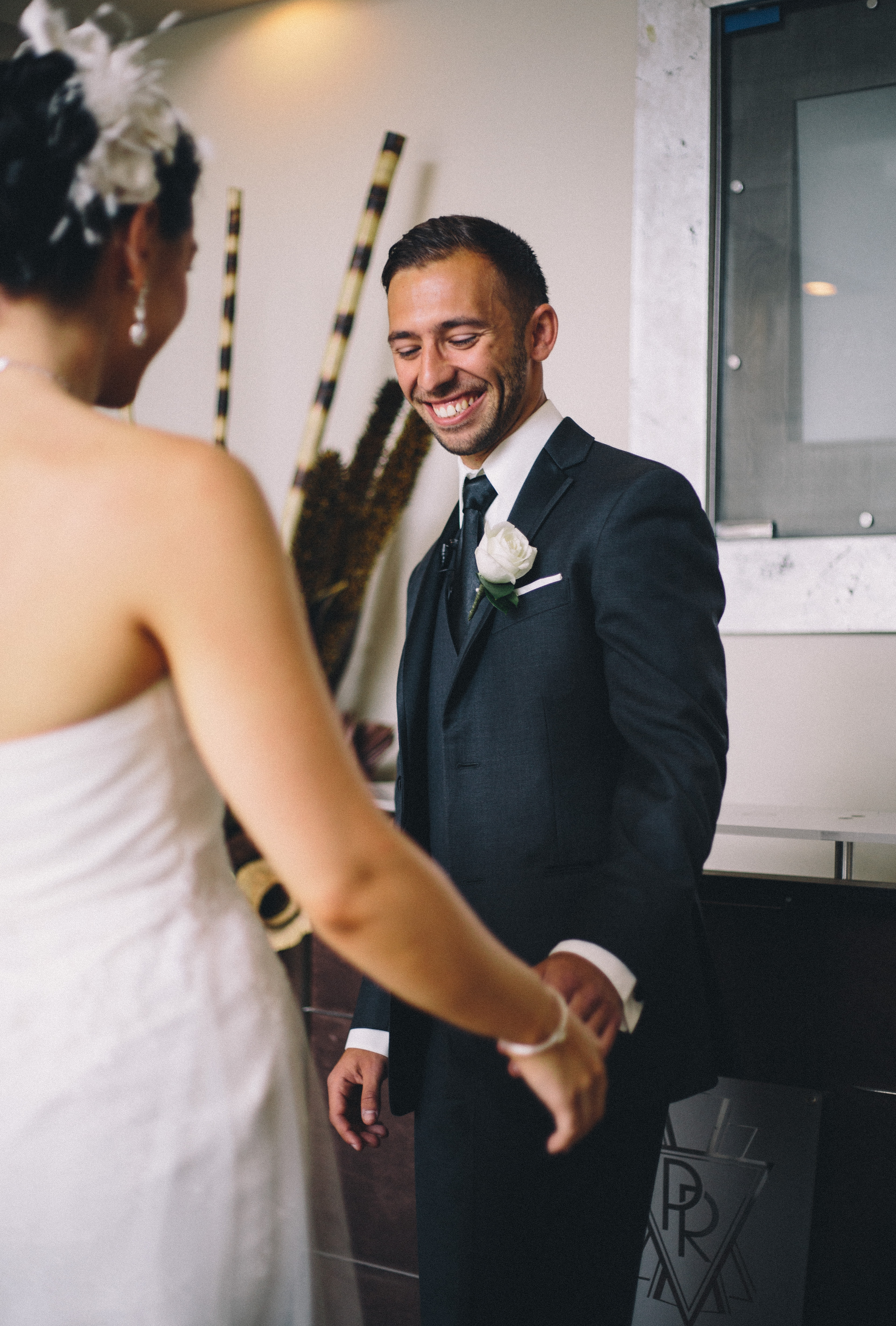 Jewish groom reacts with large grin and holds the hand of his bride during their First Look at the Palais Royale in Toronto