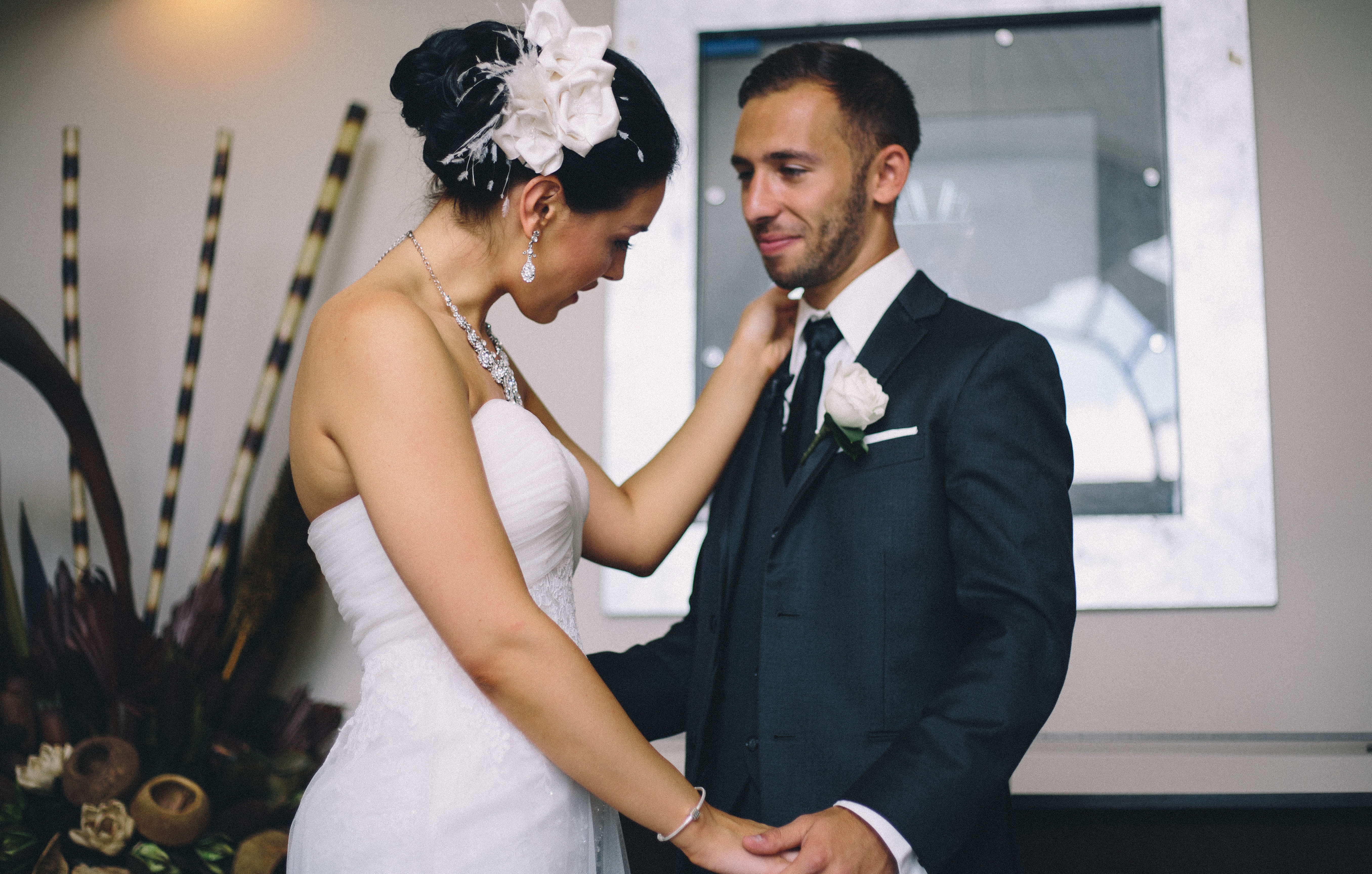 Jewish Groom tears up at his first sight of his bride wearing a sweetheart neckline wedding gown with statement diamond necklace and feathered hair piece at their First Look