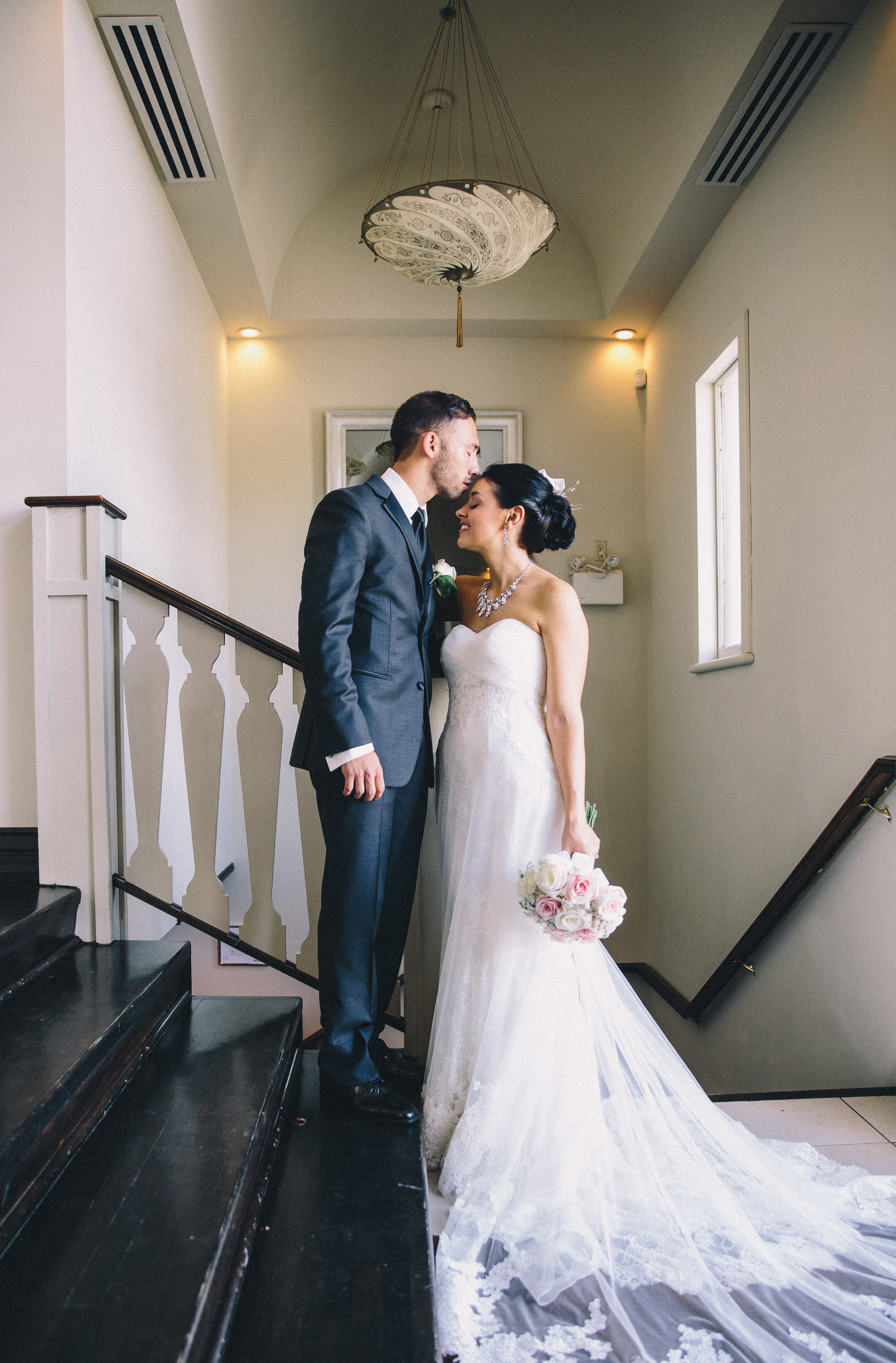 Jewish groom kisses the head of his bride in the foyer of the Palais Royale in Toronto