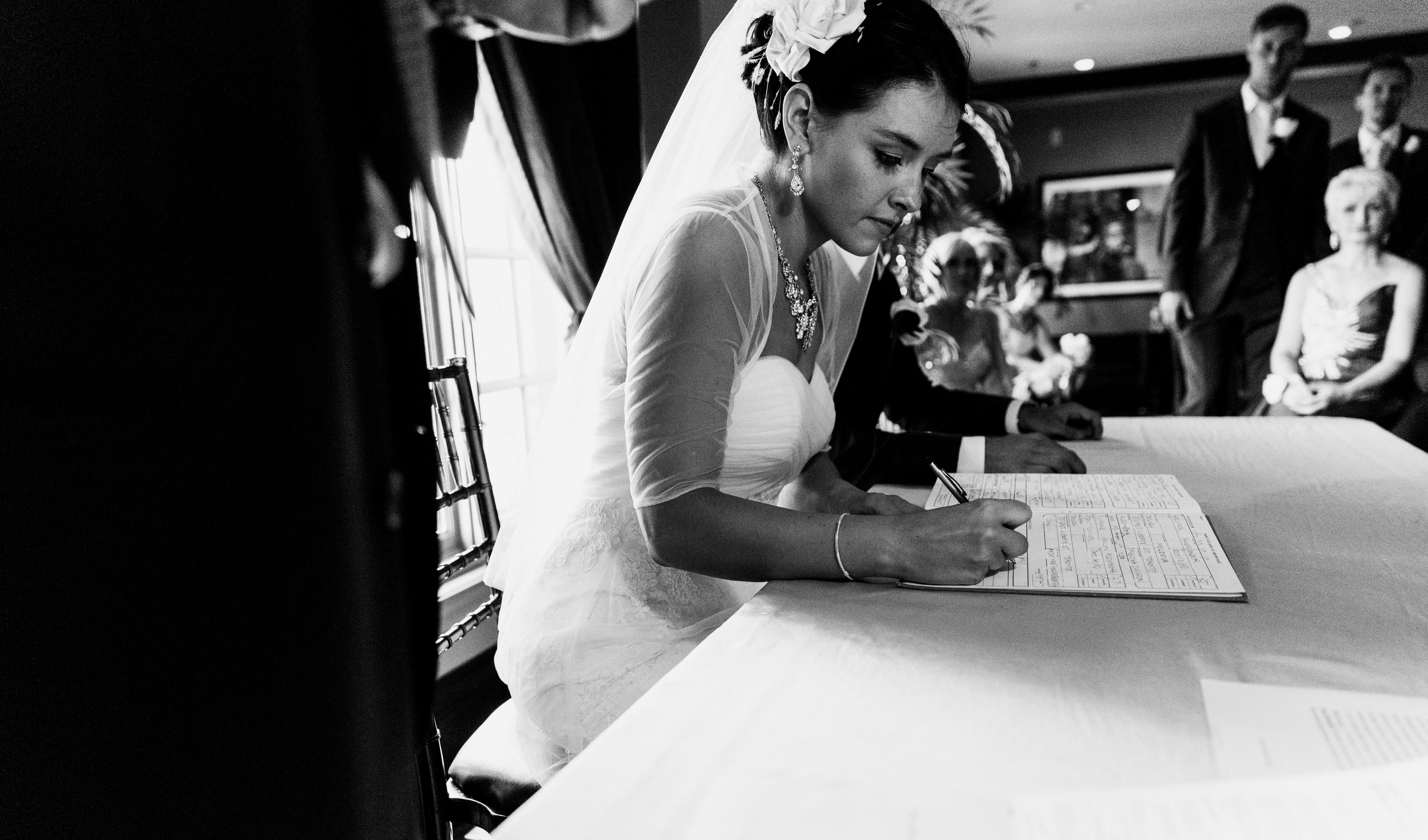 Jewish bride wearing sweetheart wedding gown and chiffon shawl signs the ketubah at Palais Royale in Toronto