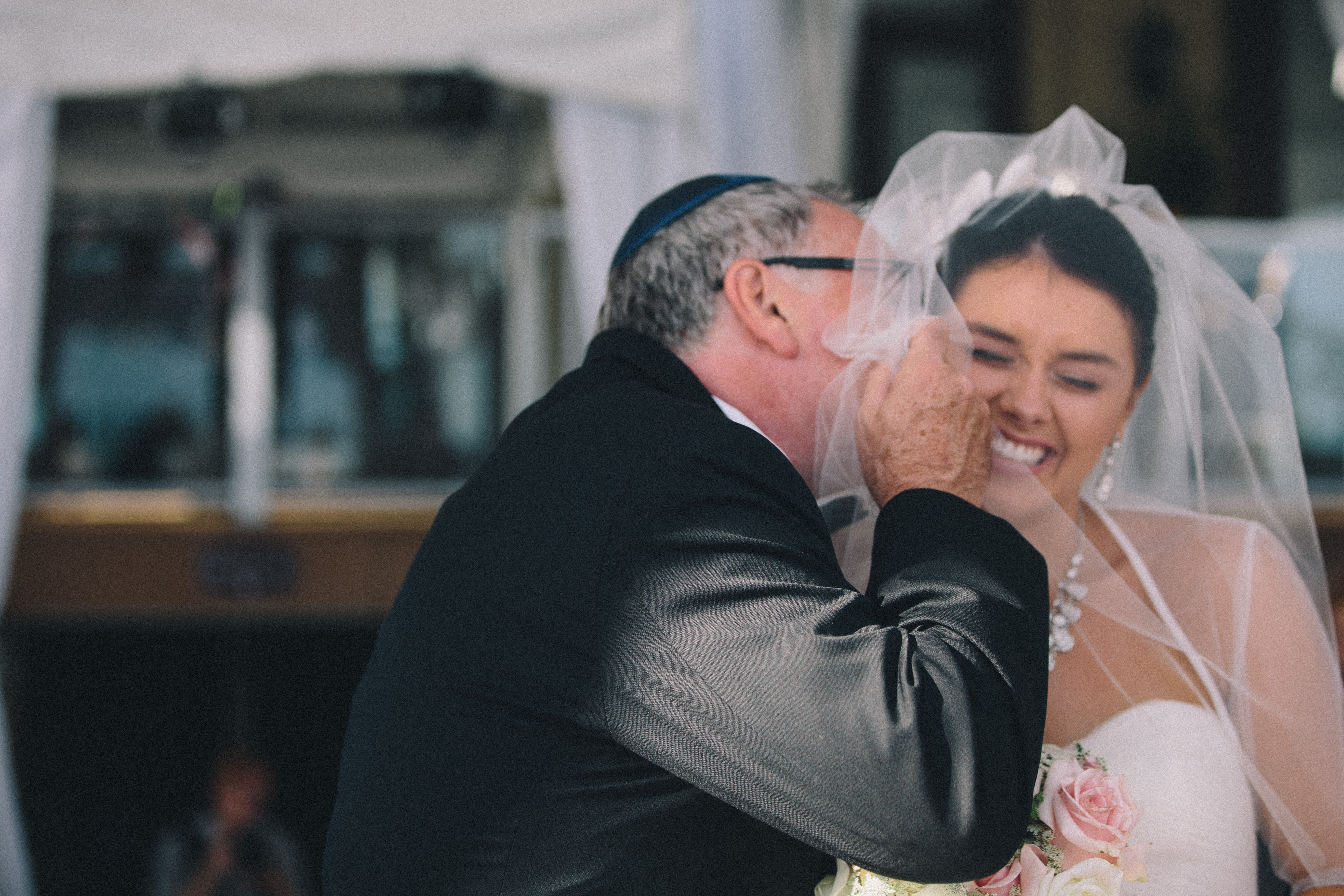 Jewish Father of the bride gives his daughter a huge kiss before giving her away at the Palais Royale in Toronto