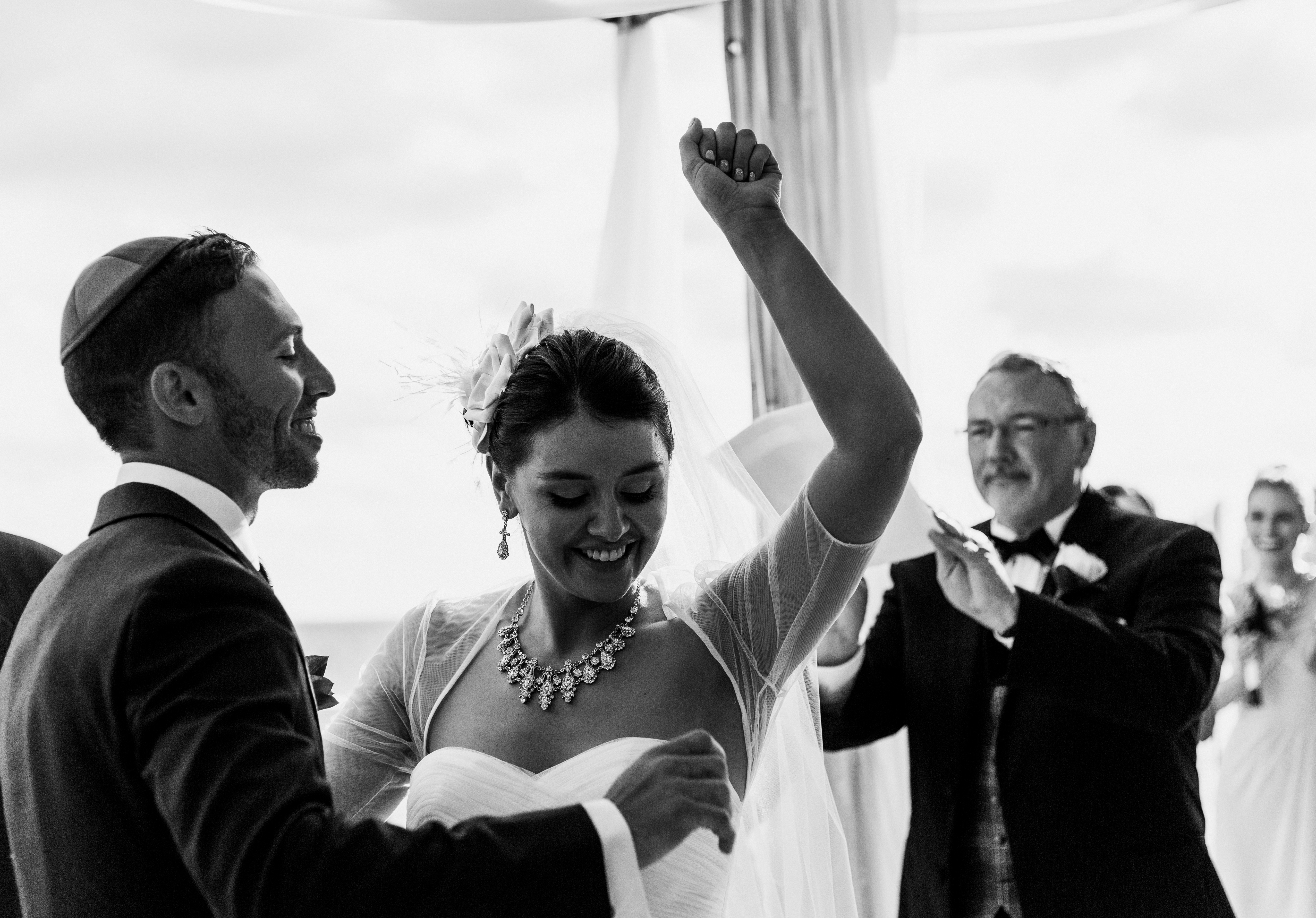 Jewish bride wearing a sweetheart wedding gown with statement diamond necklace gives a fist pump as they are pronounced man and wife