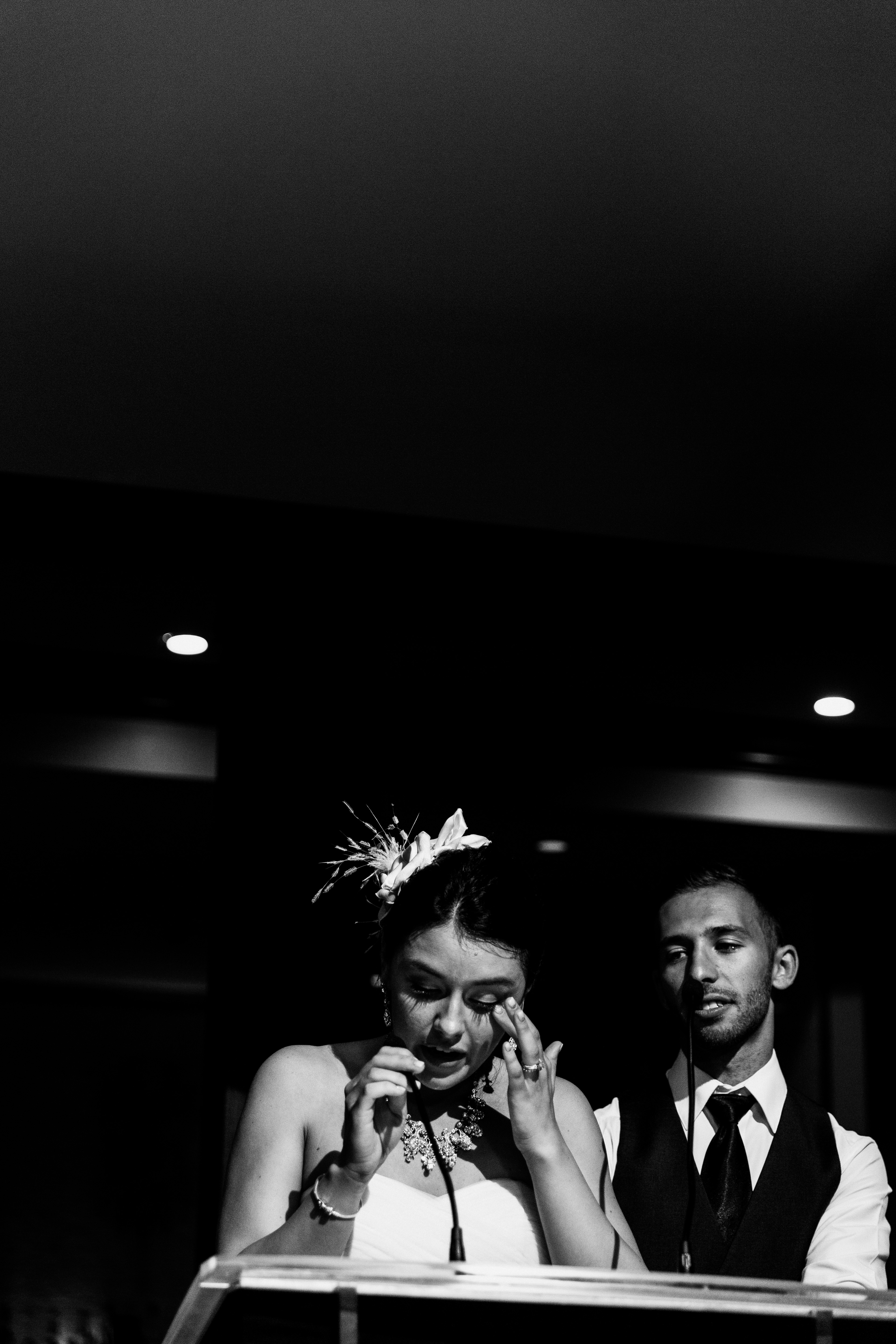 Jewish bride wearing feathered hair piece tears up while giving her thank you speech during wedding reception at the Palais Royale