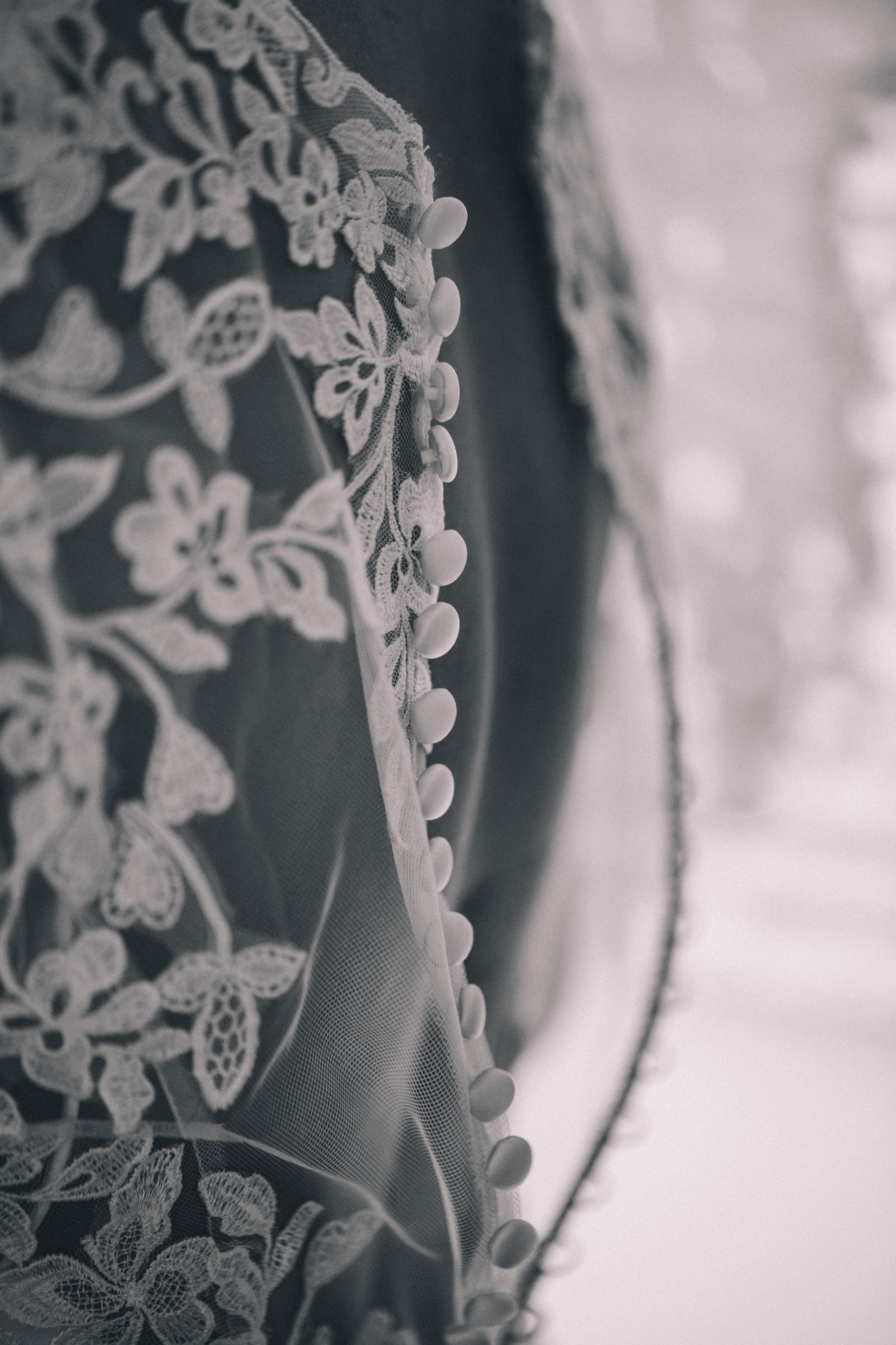 Buttons on the back of a lace wedding dress before interracial wedding in Toronto