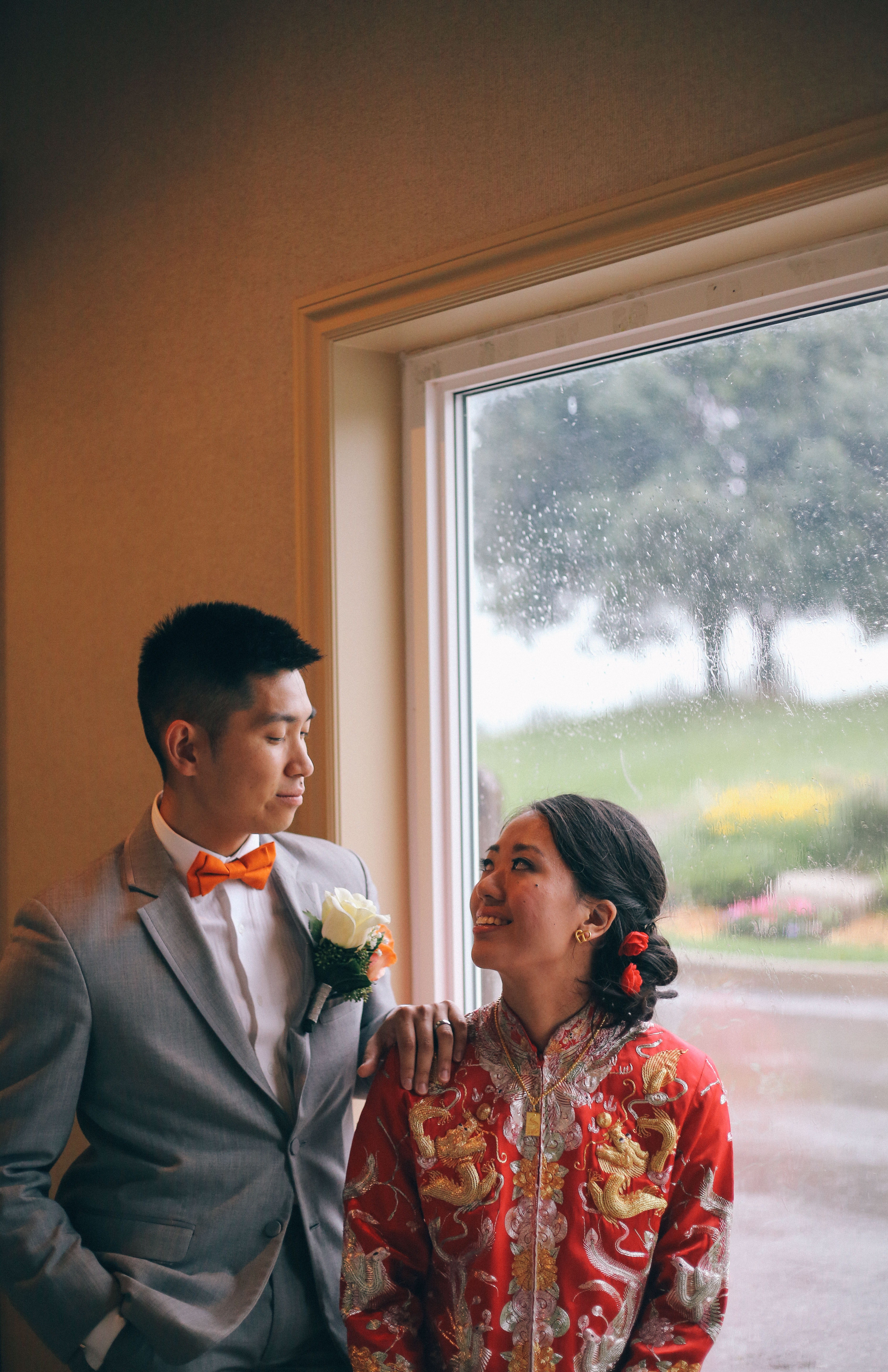 A bride in traditional Chinese cheongsam stands at a window and looks up at her groom wearing an orange bowtie at the Mandarin Country Club