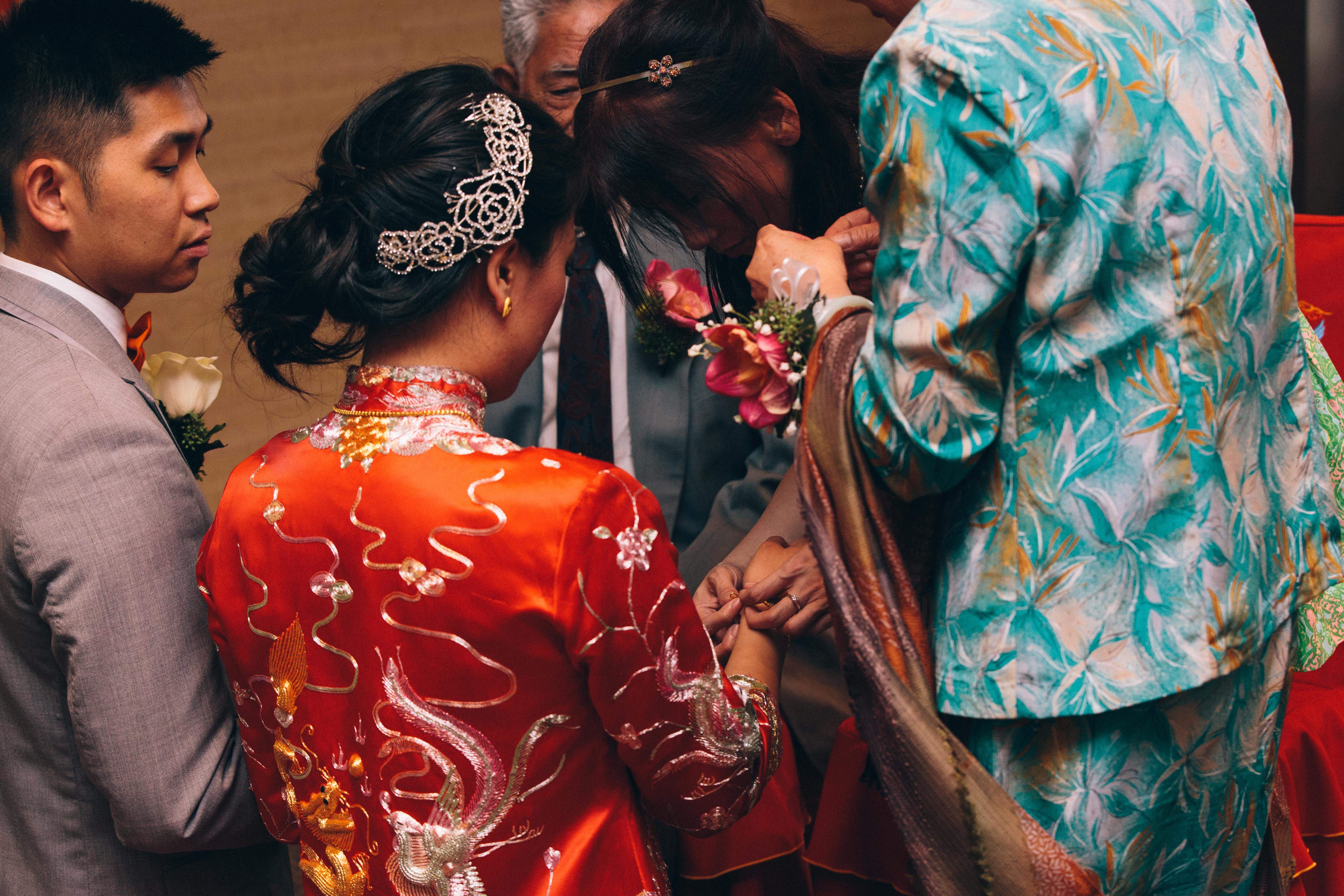 Chinese groom looks on as relatives fasten bracelet onto bride's wrist during Chinese tea ceremony at the Mandarin Country Club in Markham