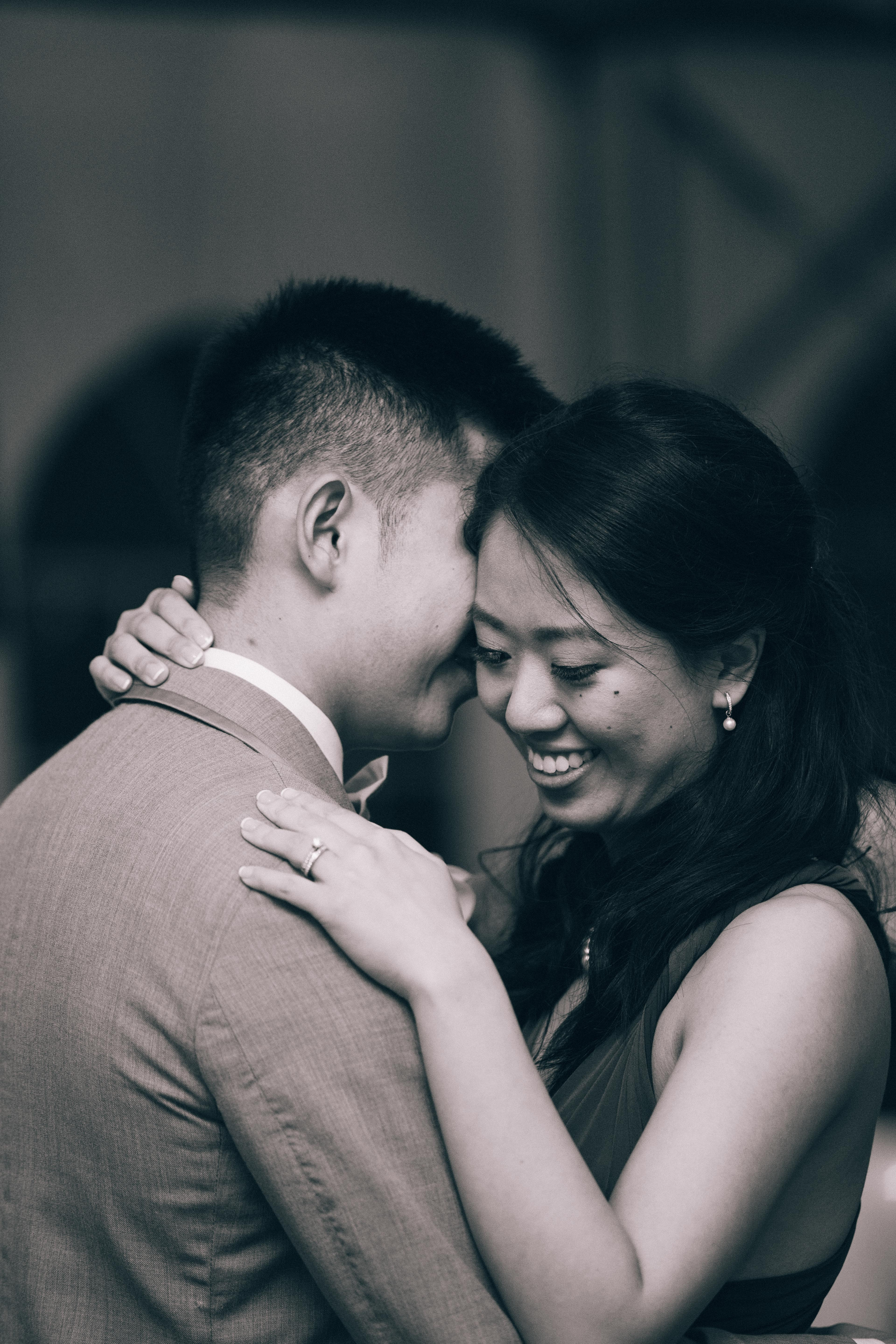 Chinese bride smiles during first dance as groom kisses her on the cheek at wedding reception at the Mandarin Country Club