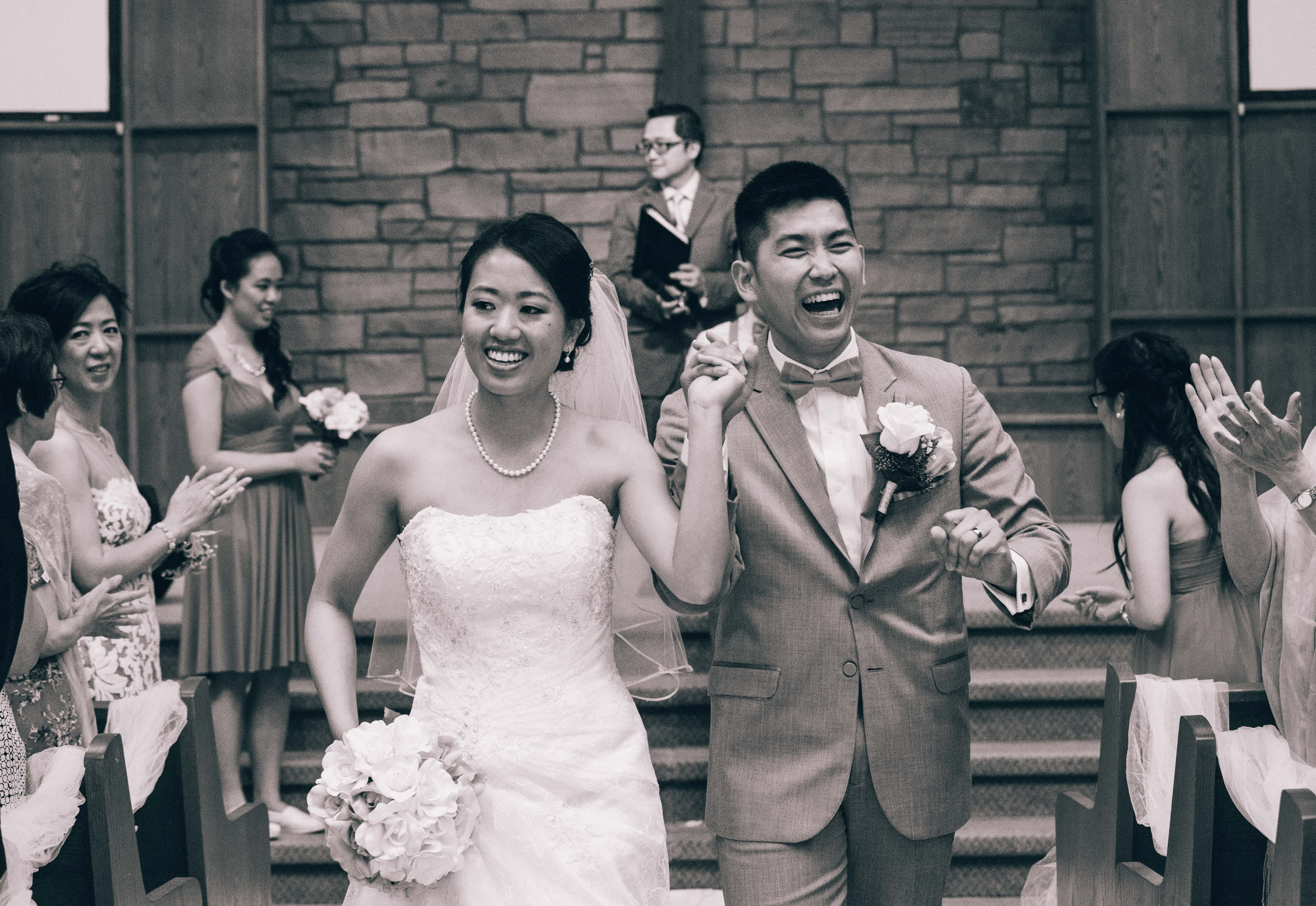 Chinese bride and groom jubilantly walking down the aisle after getting married