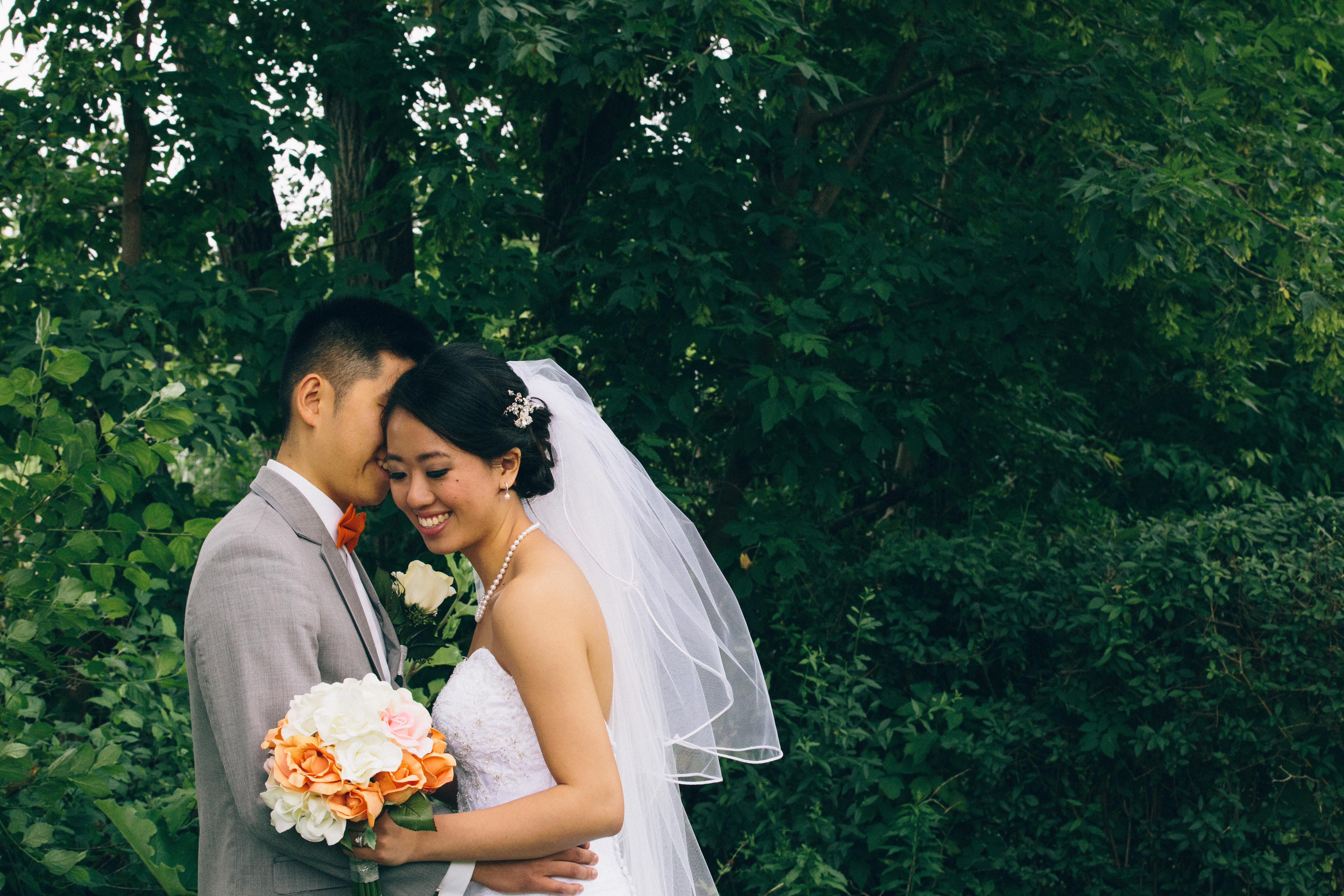 Chinese groom whispers into the ear of his bride looks down at her bouquet wearing a sweetheart wedding gown and veil with hairpiece