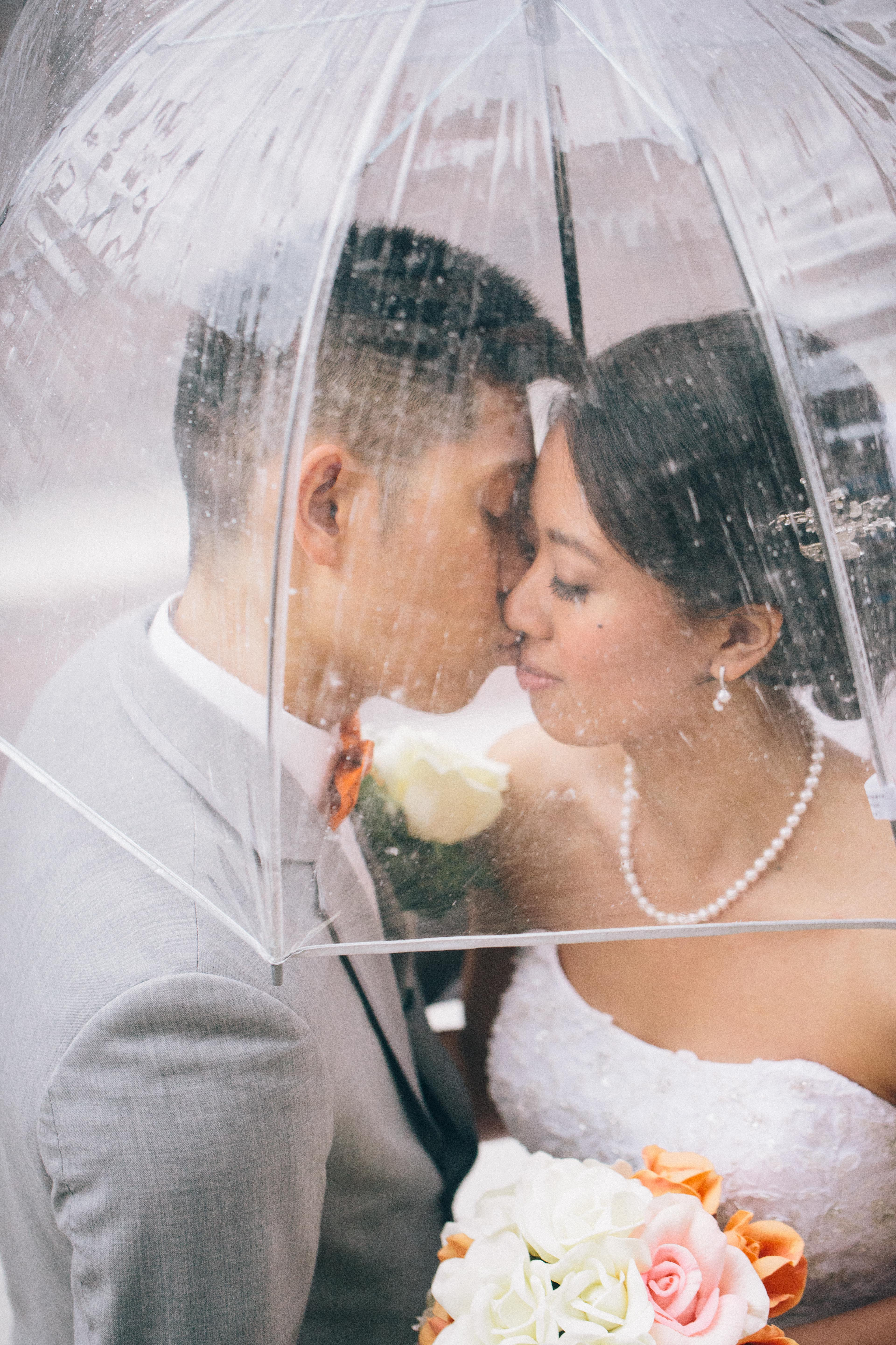 Chinese bride and groom share a kiss under a clear umbrella during their summer wedding in Toronto