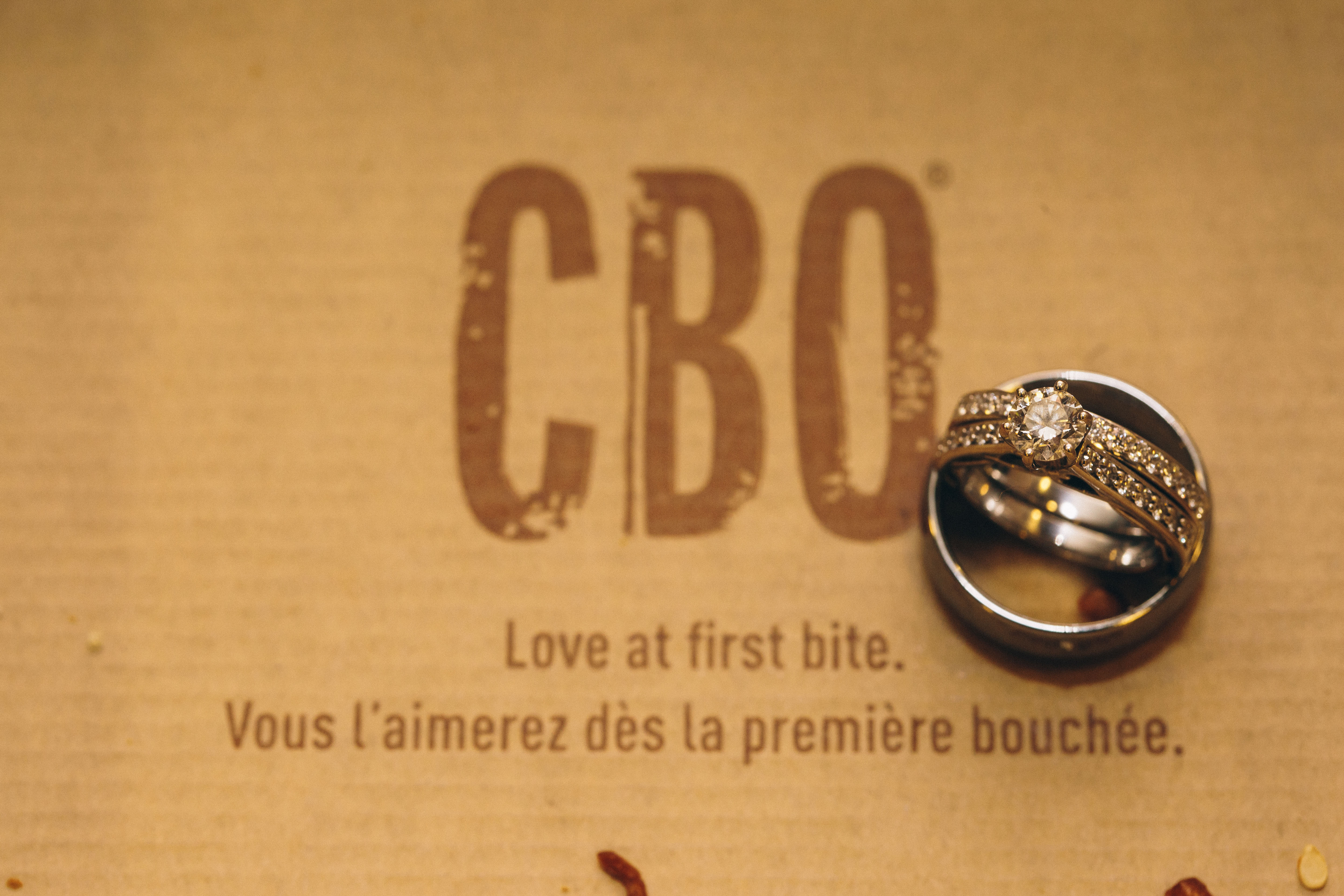 "An engagement ring and wedding ring on top of McDonald's CBO carton saying the words ""love at first bite"""