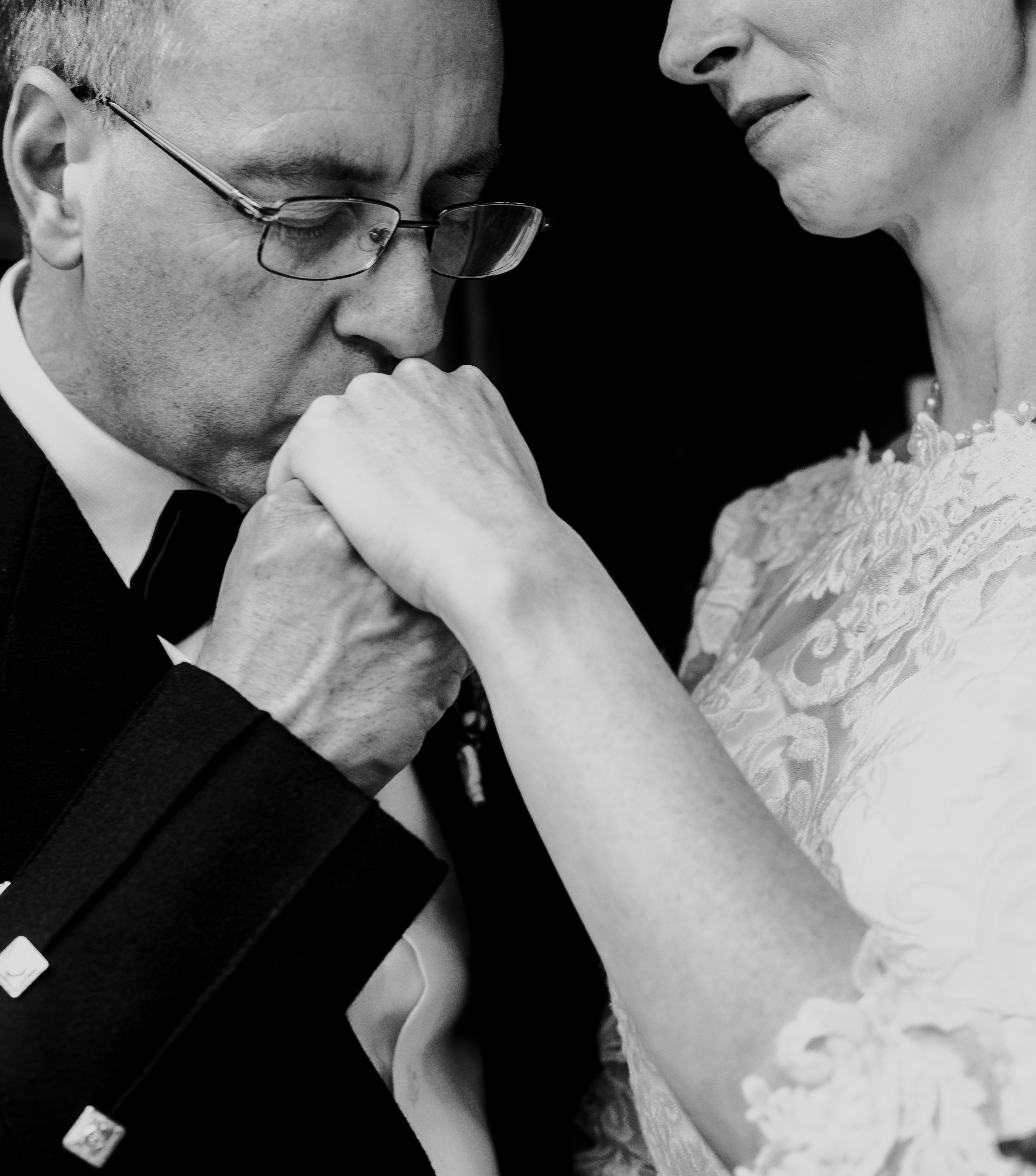 Groom in traditional Scottish dress kisses the hand of his bride during a fall wedding in Hamilton Ontario