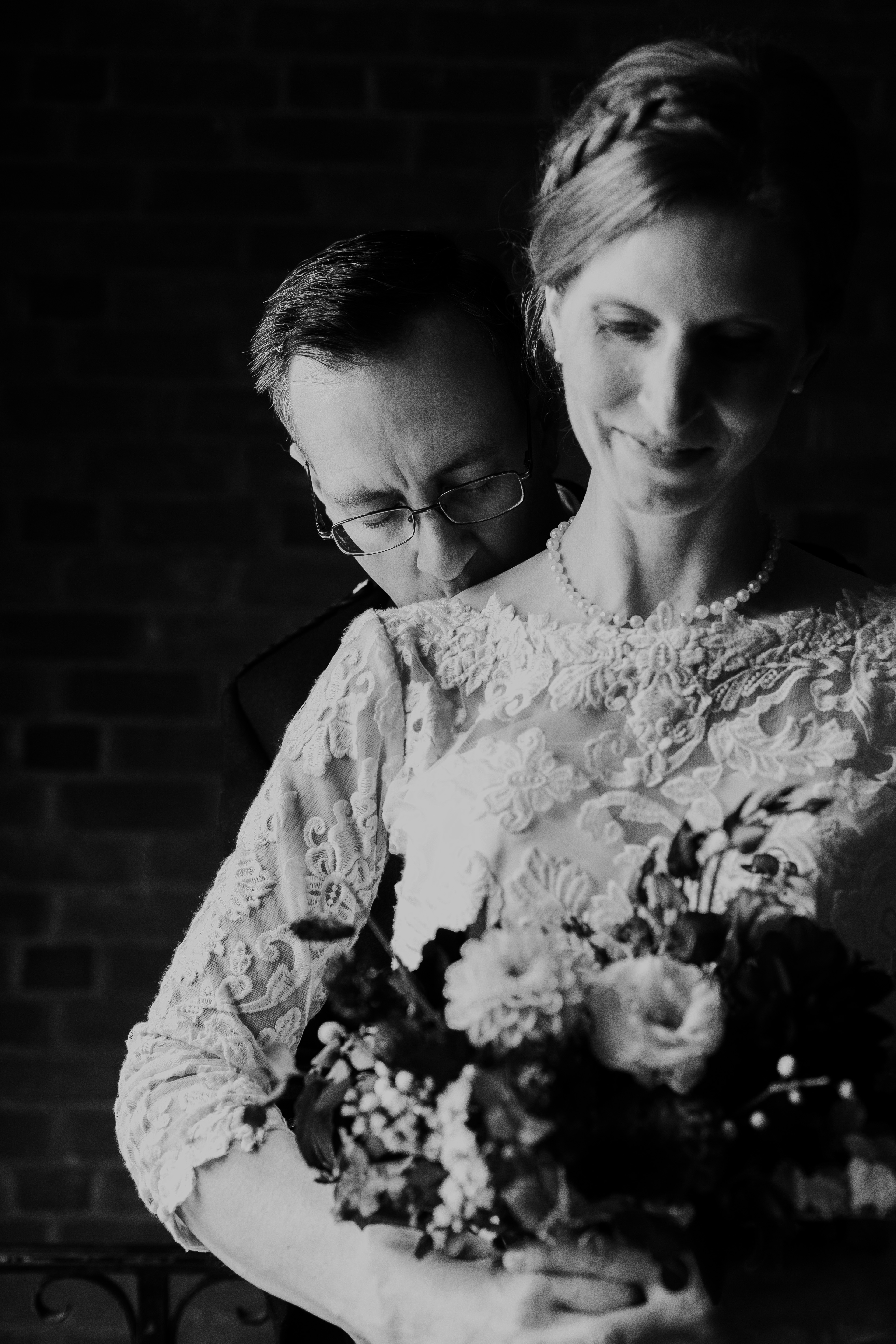 Groom kissing the bride's shoulder as she stands to show the lace detail of her wedding gown and pearl necklace at McMaster University Club