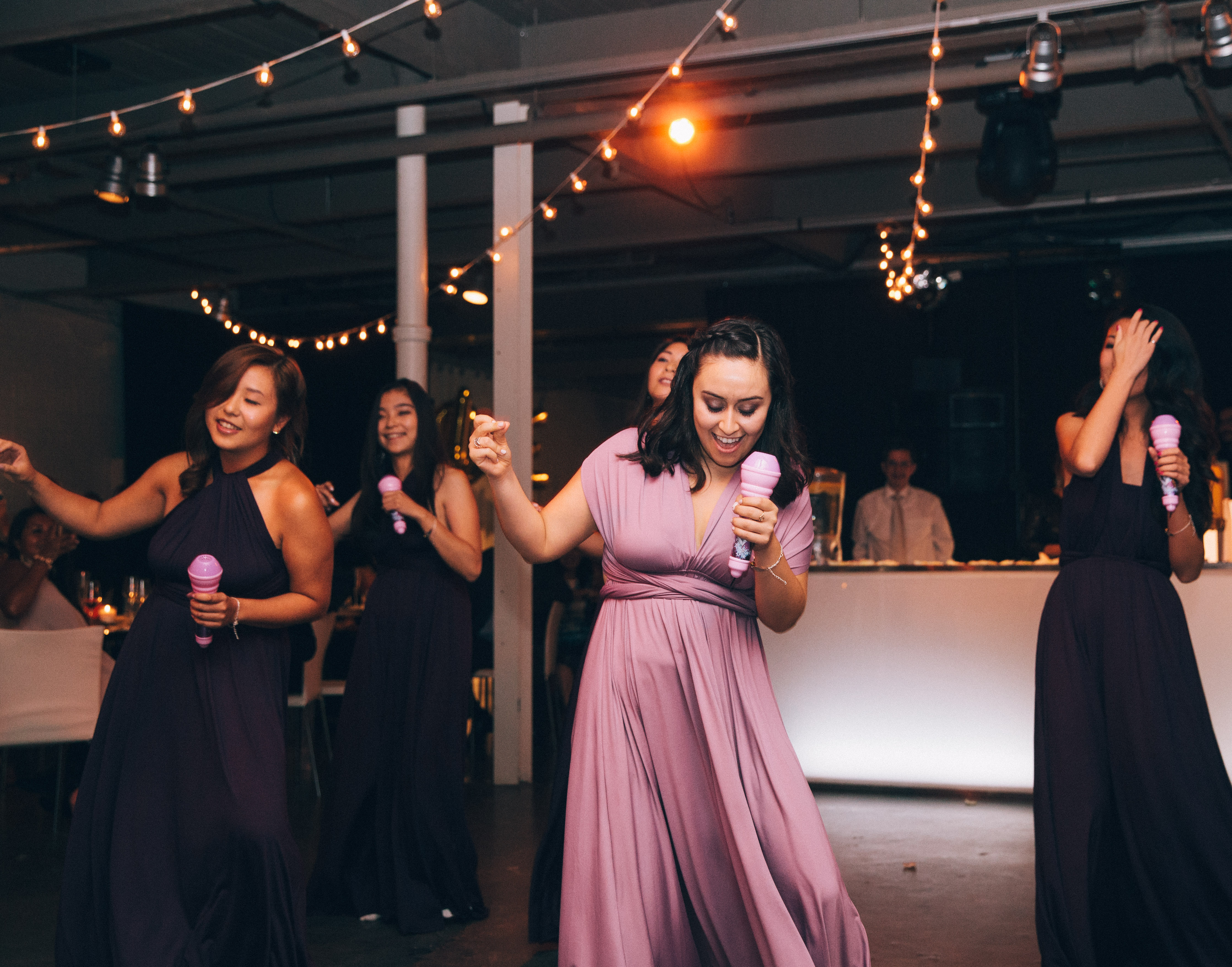 Bridesmaids wearing purple wrap dresses perform a dance number at wedding reception in Montreal