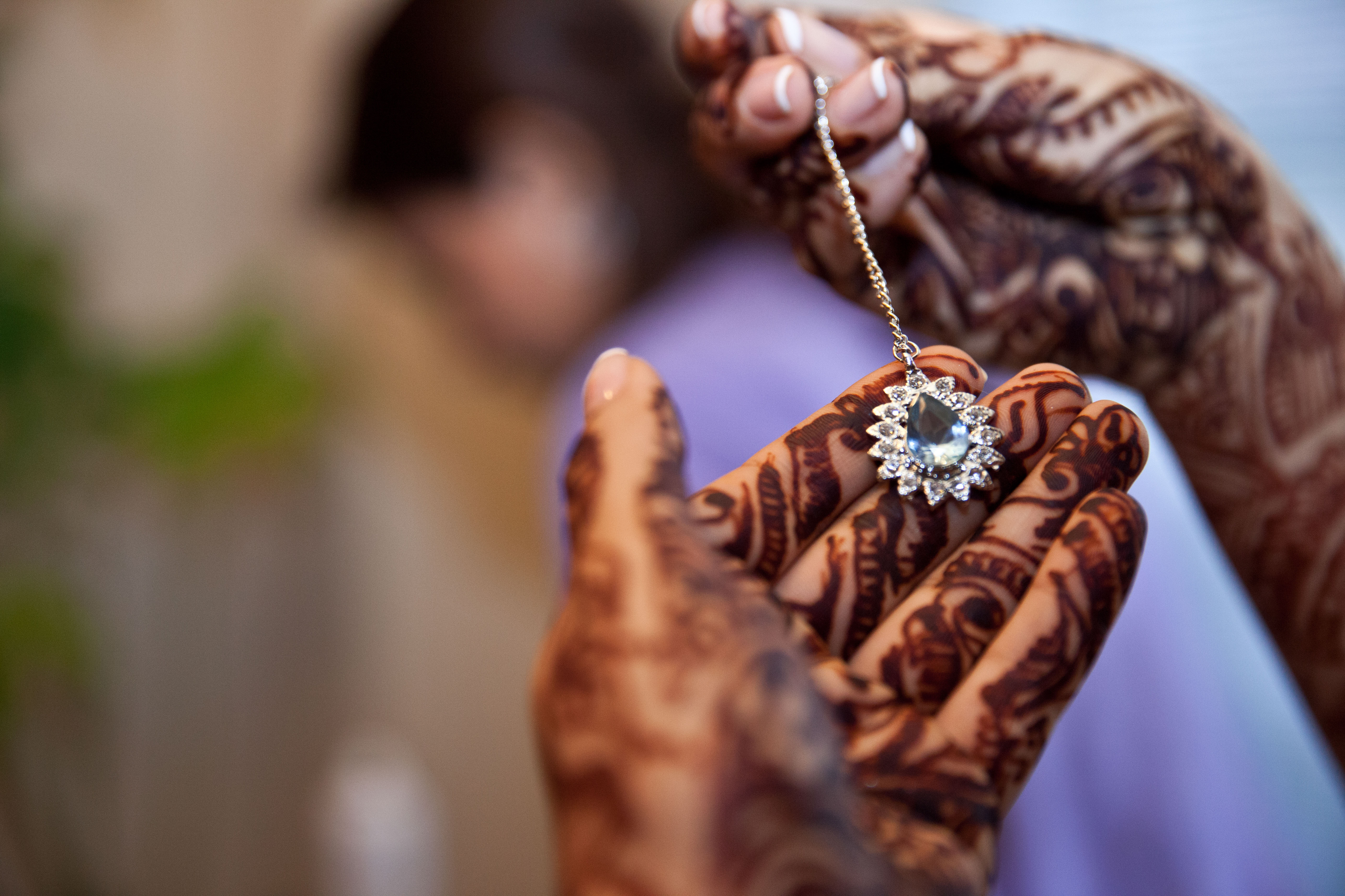 Close up of mendhi hands holding teardrop pendant on a chain at Muslim wedding in Toronto