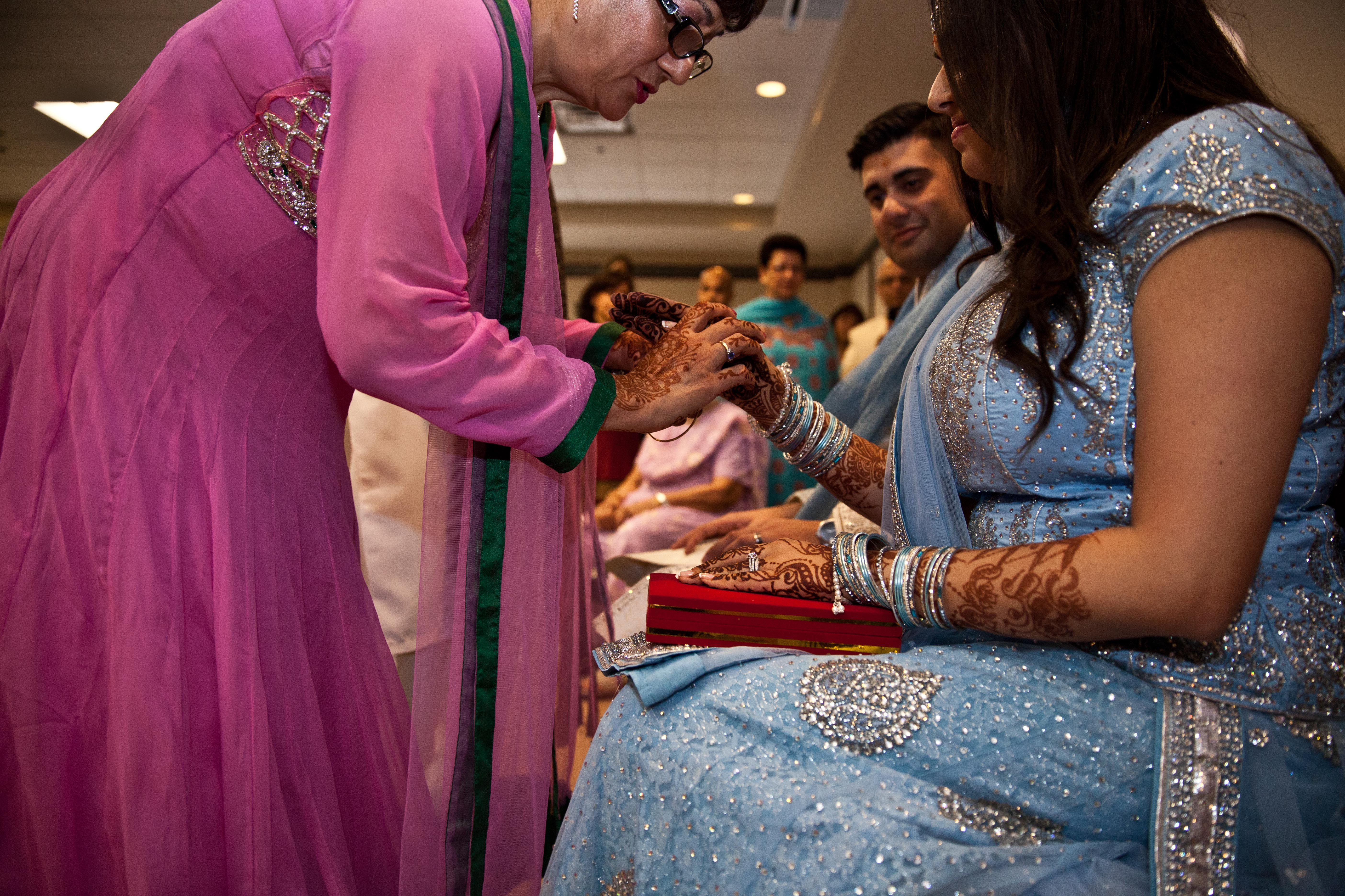 Mother of the groom slipping bangles on the bride's wrists during the Puro ceremony in a Toronto Ismaili Muslim wedding