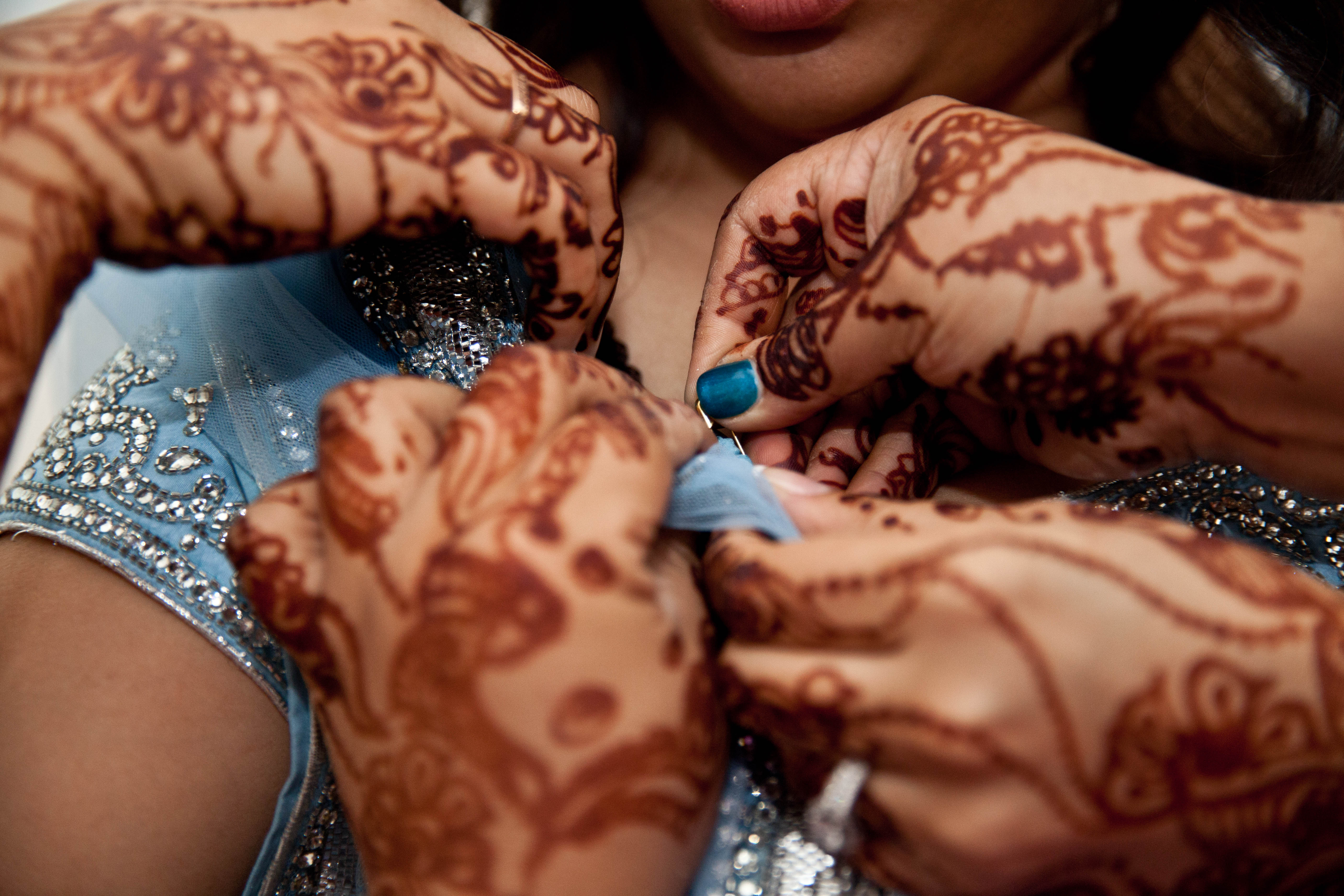 Multiple hands with mendhi on them helping bride fasten her sari