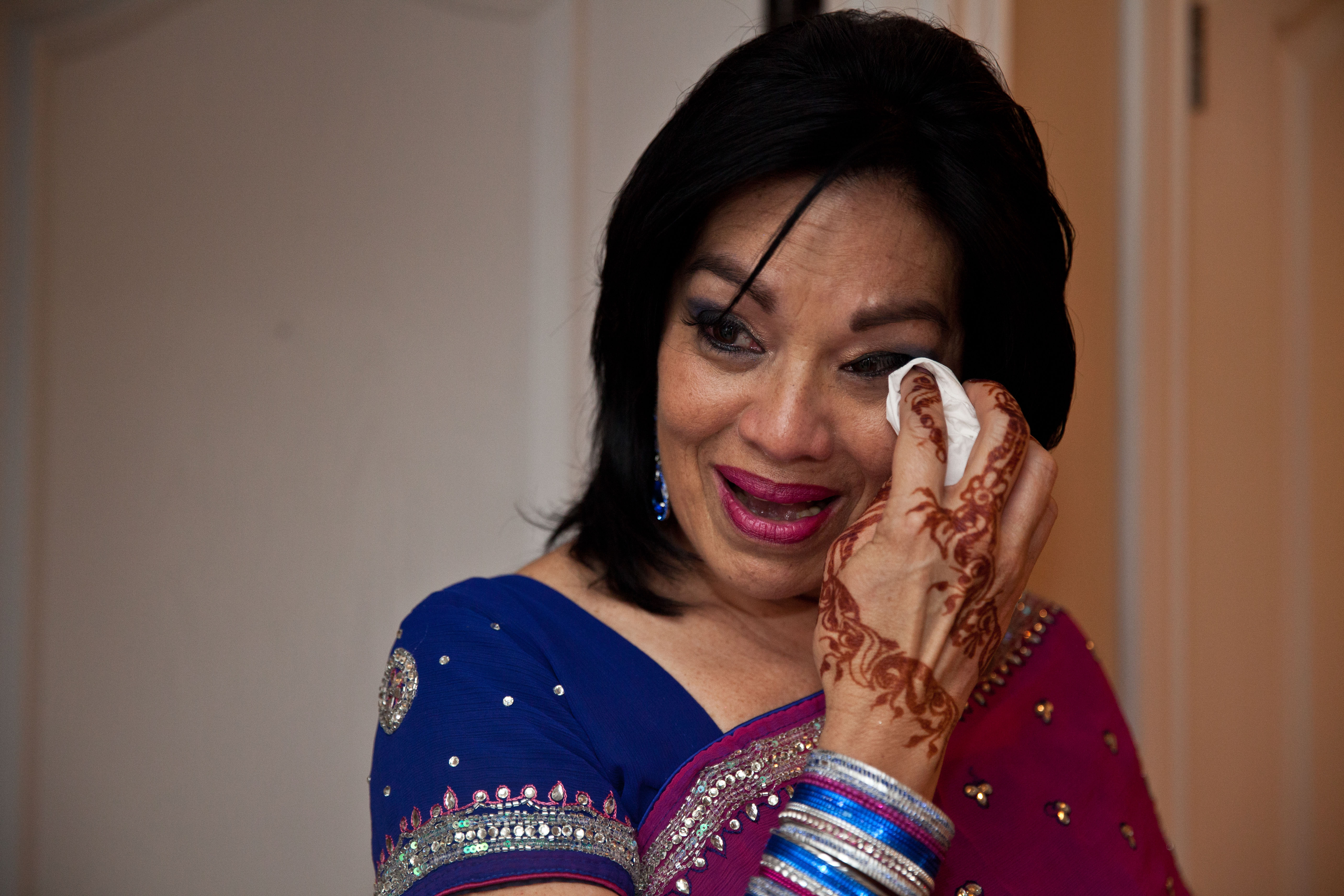 Mother of the bride wearing blue and pink sari wiping tear from her eye as she sees the bride