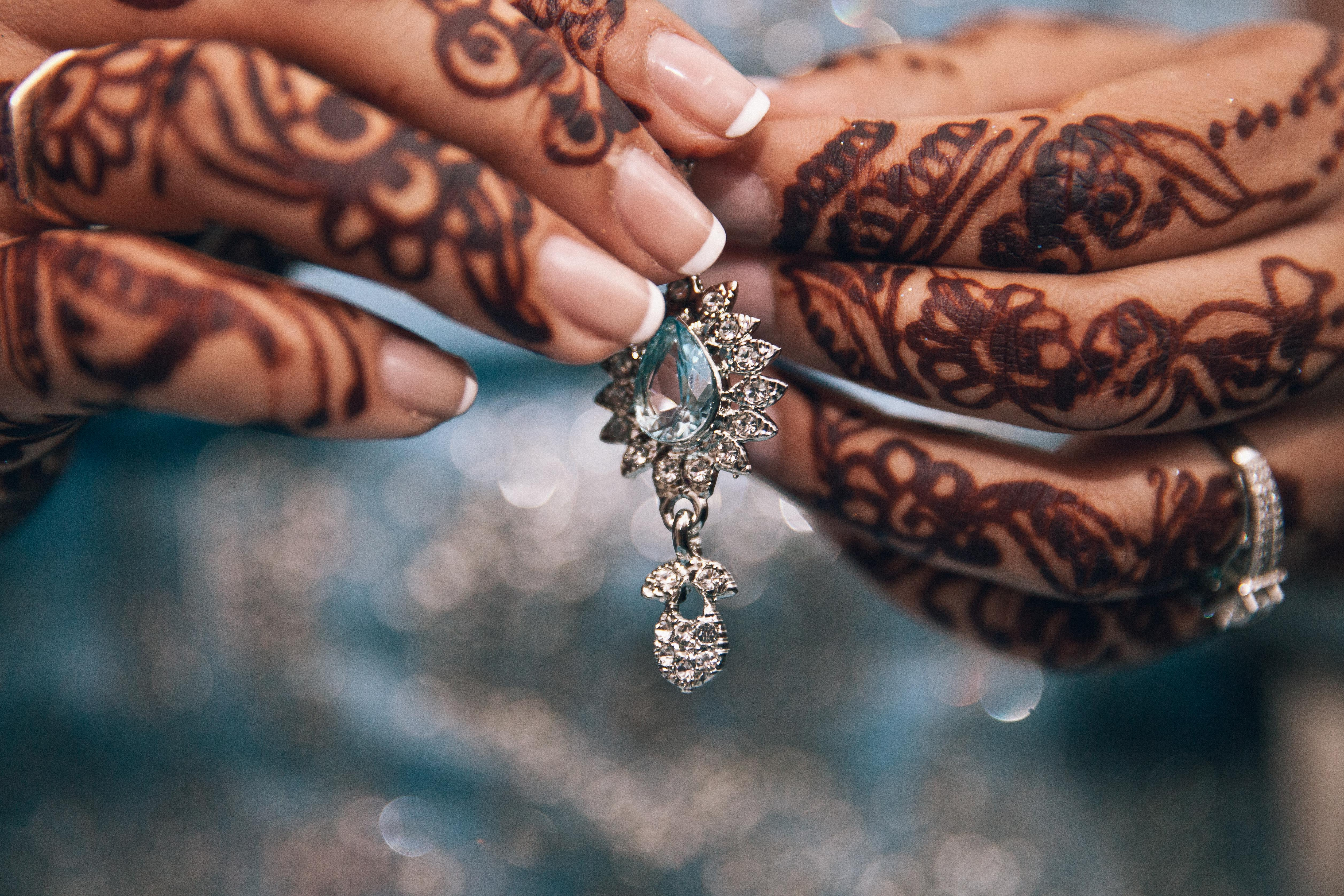 Hands with mendhi on them holding blue drop earring