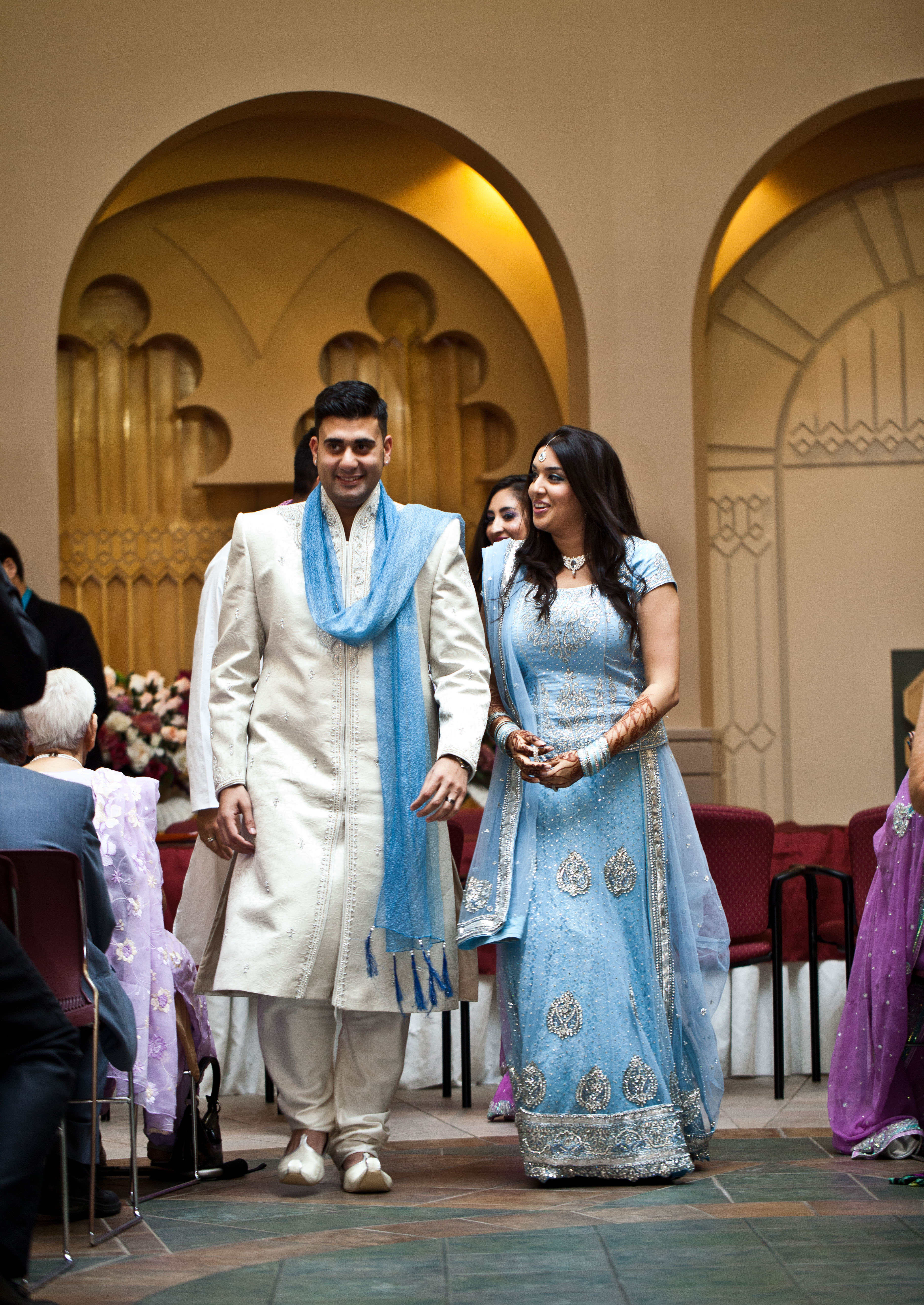 Bride and groom beaming as they walk down toward the camera after the Nikkah during a Toronto Ismaili Muslim wedding