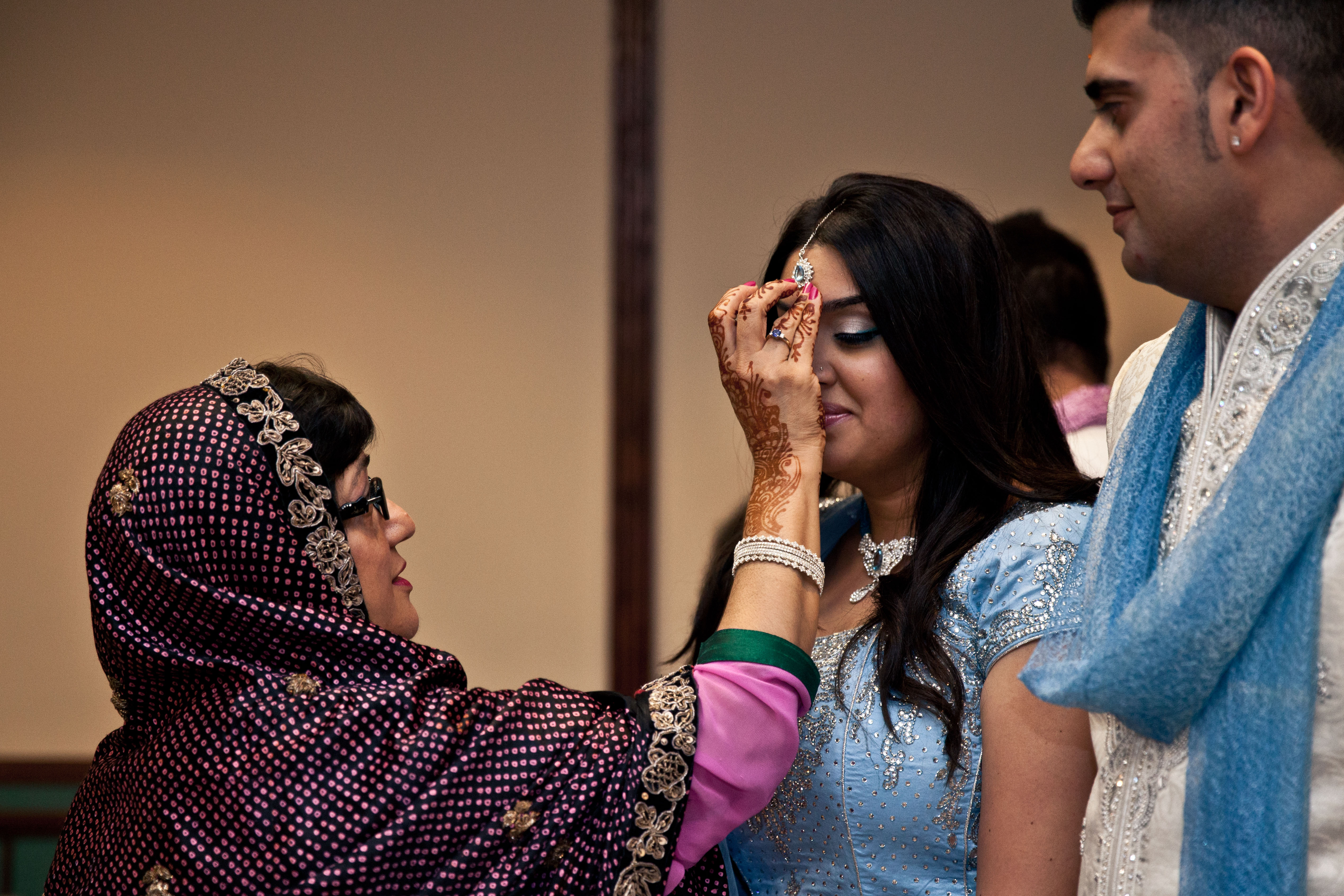Mother of the groom placing the chandlo or dot of saffron water on the bride's forehead in the Ponkwa ceremony during a Toronto Ismaili Muslim wedding