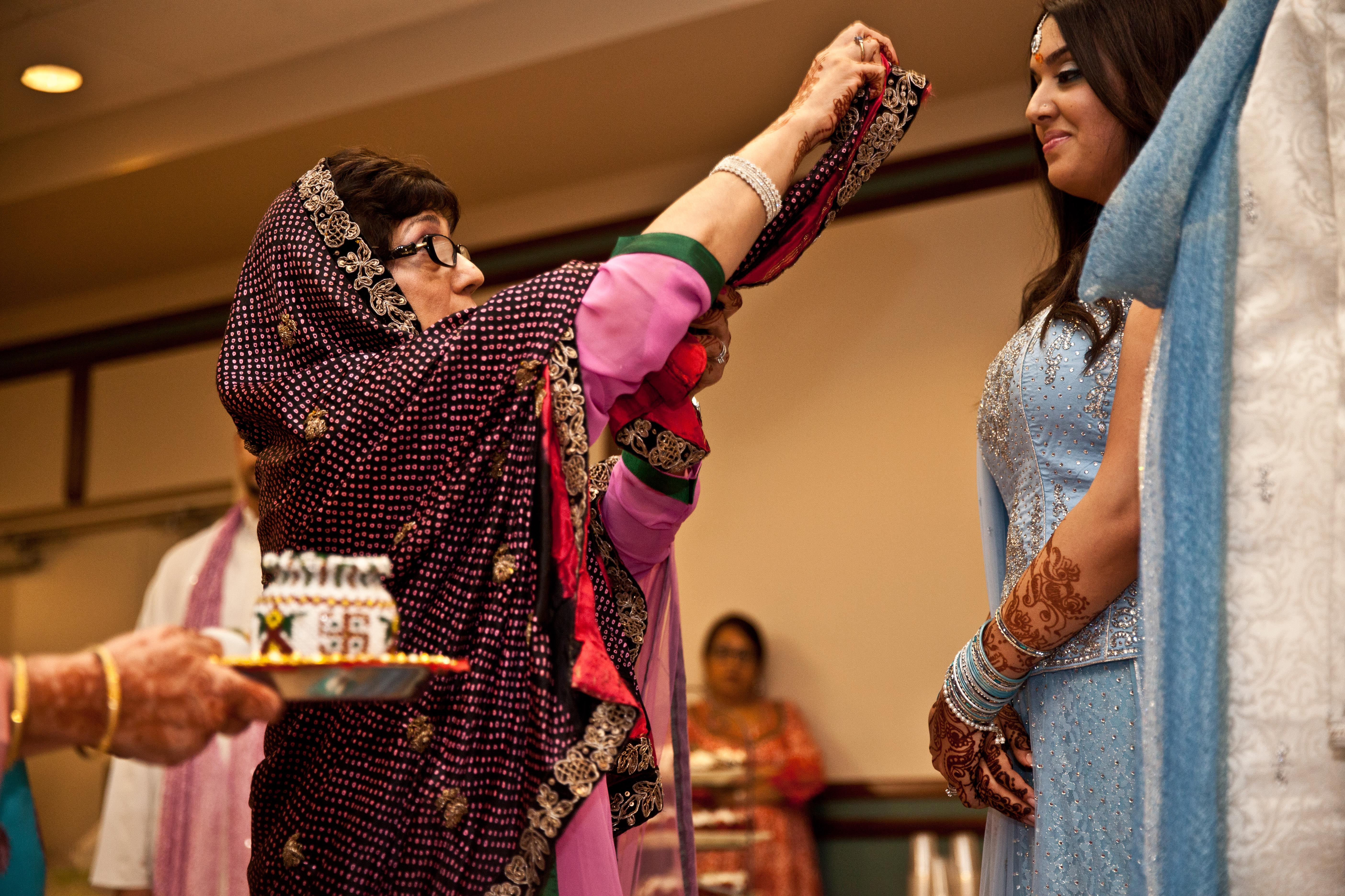 Mother of the groom blessing the married couple during the Ponkwa ceremony in a Toronto Ismaili Muslim wedding